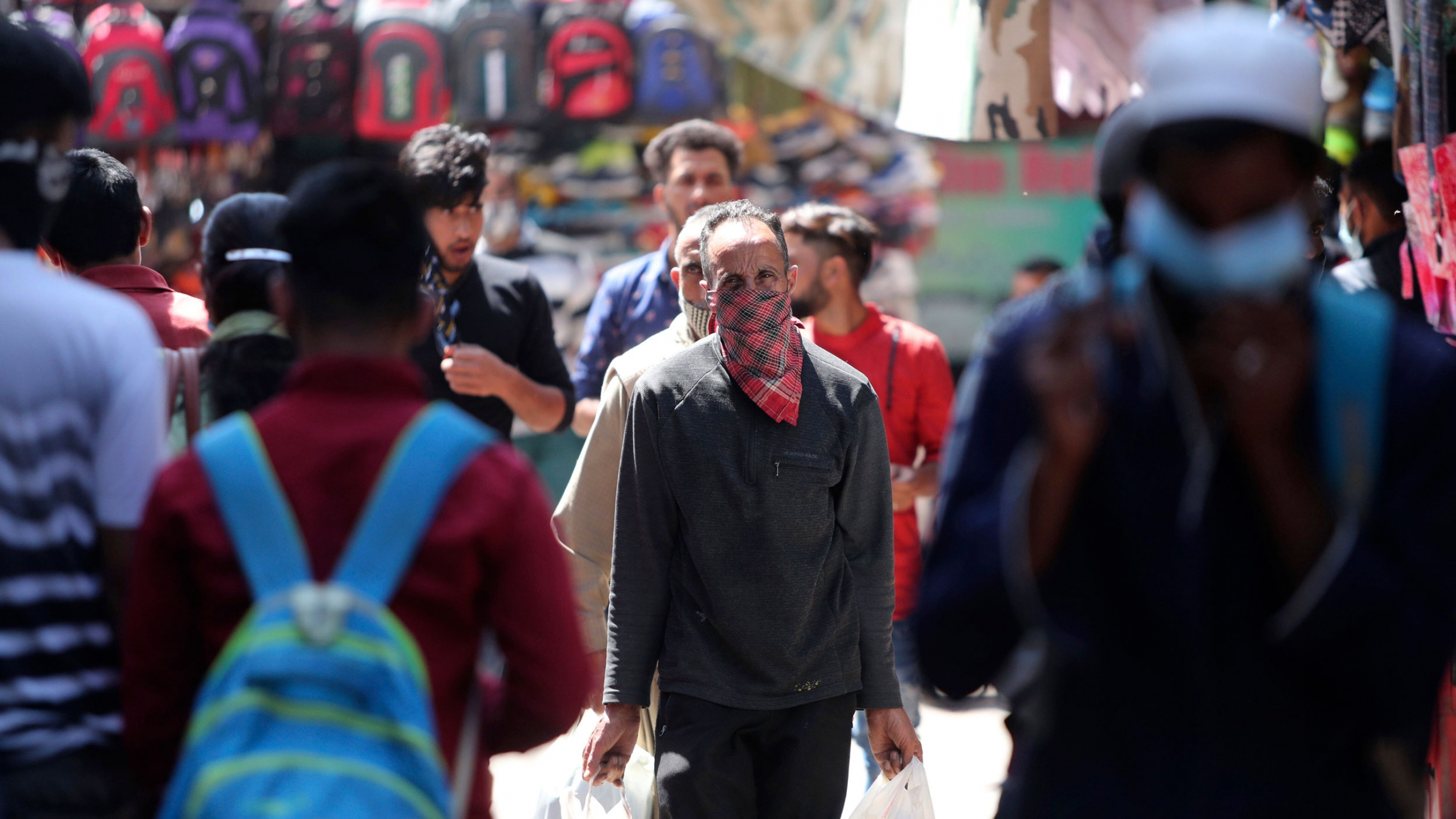 A crowd of people are shown in the street with one man in the center fram wearing a scarf over his face.