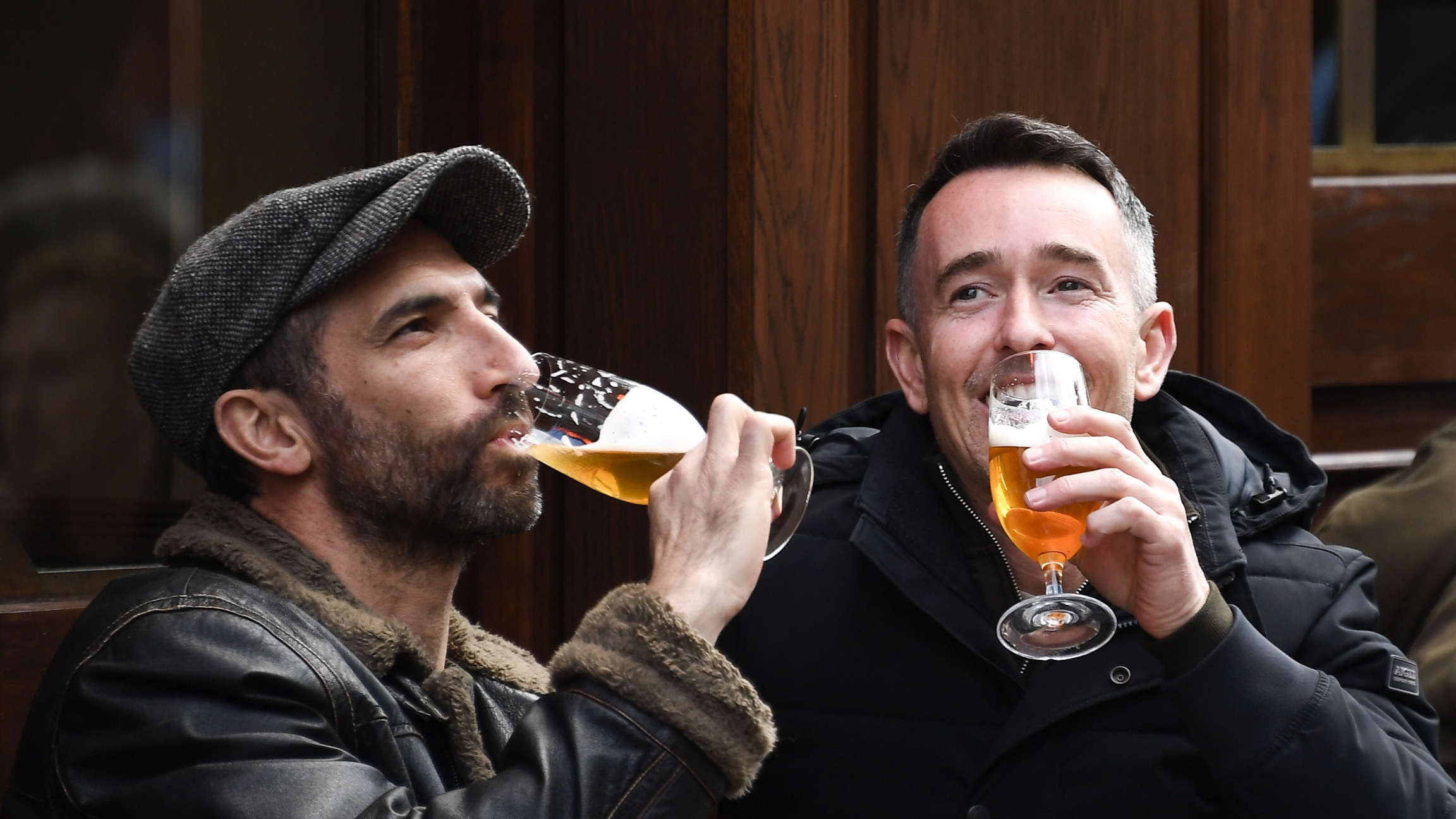 Two white men wearing dark jackets drink beer outdoors at a pub in London.
