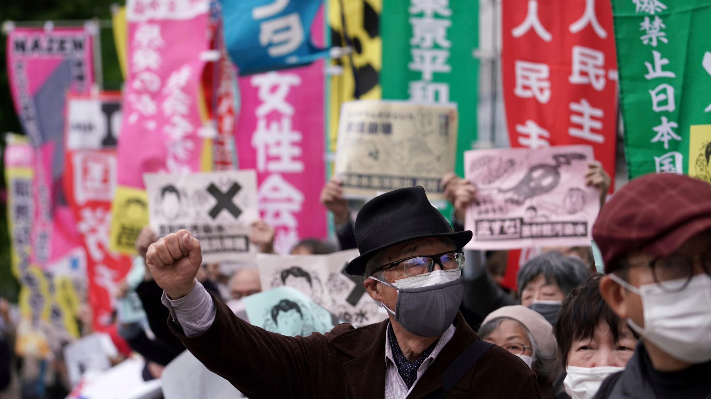 A man is shown among a crowd of protesters wearing a dark jacket, hat and face mask with his right hand in the air.