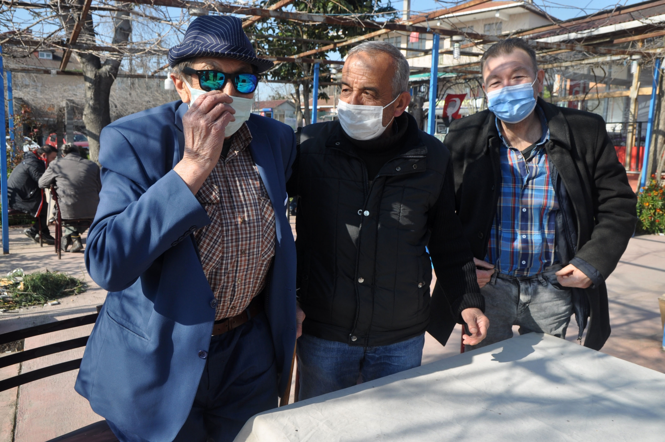 Three older men wearing blue and black clothing and face masks pose together in an outdoor tea garden.