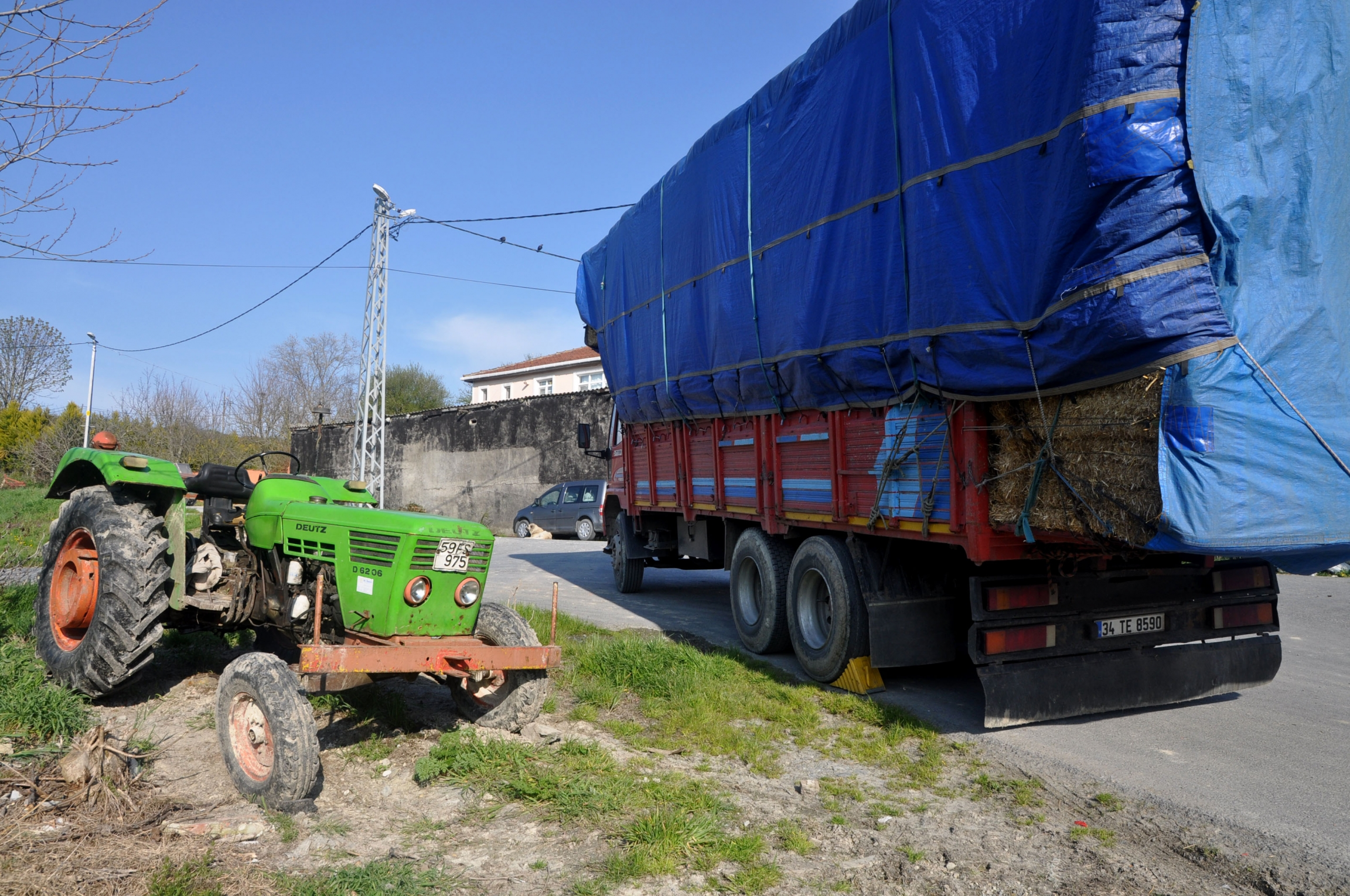 A truck with a blue cover arrives with hay, near a green tractor, on the side of the road.