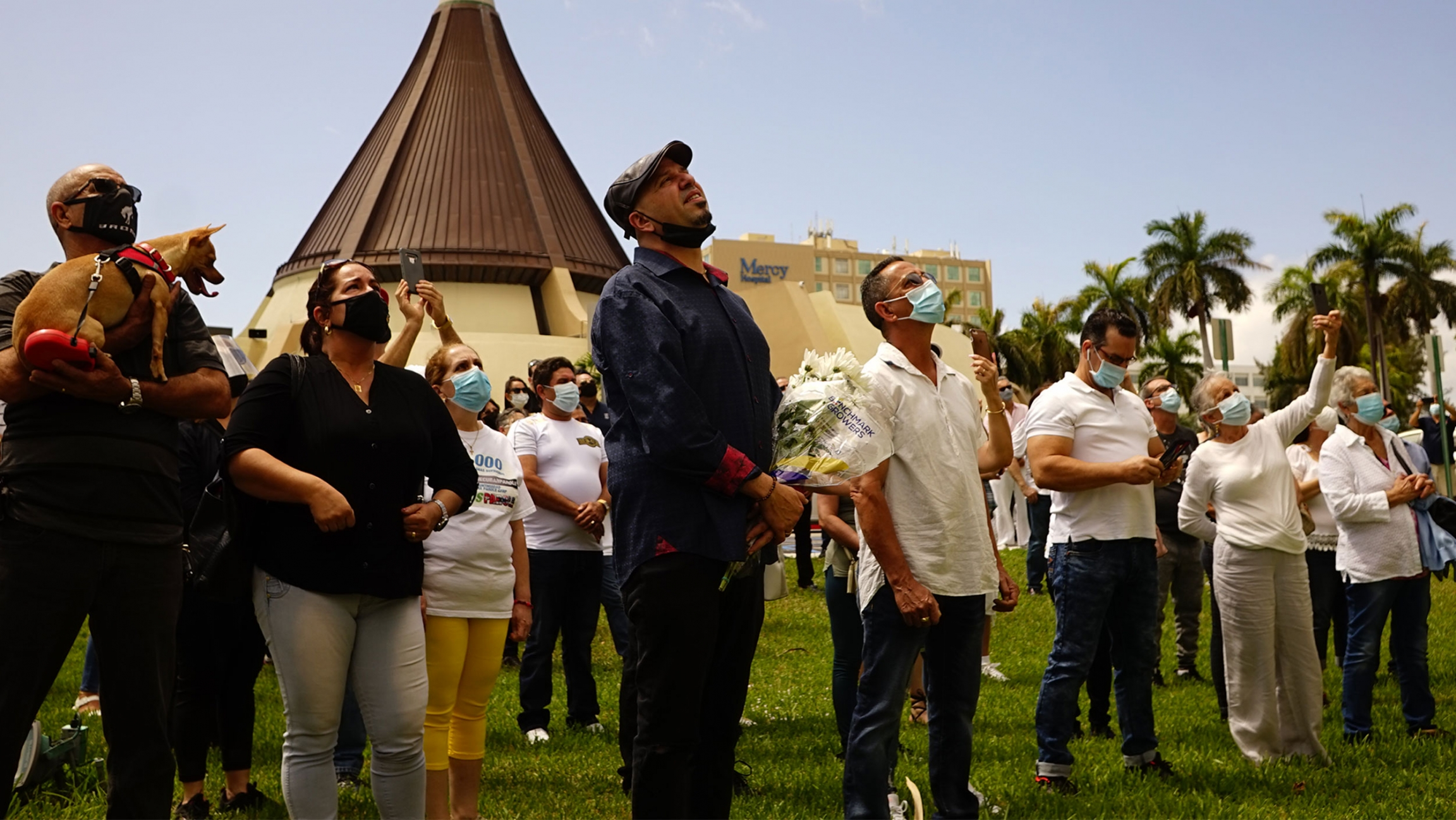 Group of people gather outside a church and look upward in prayers.