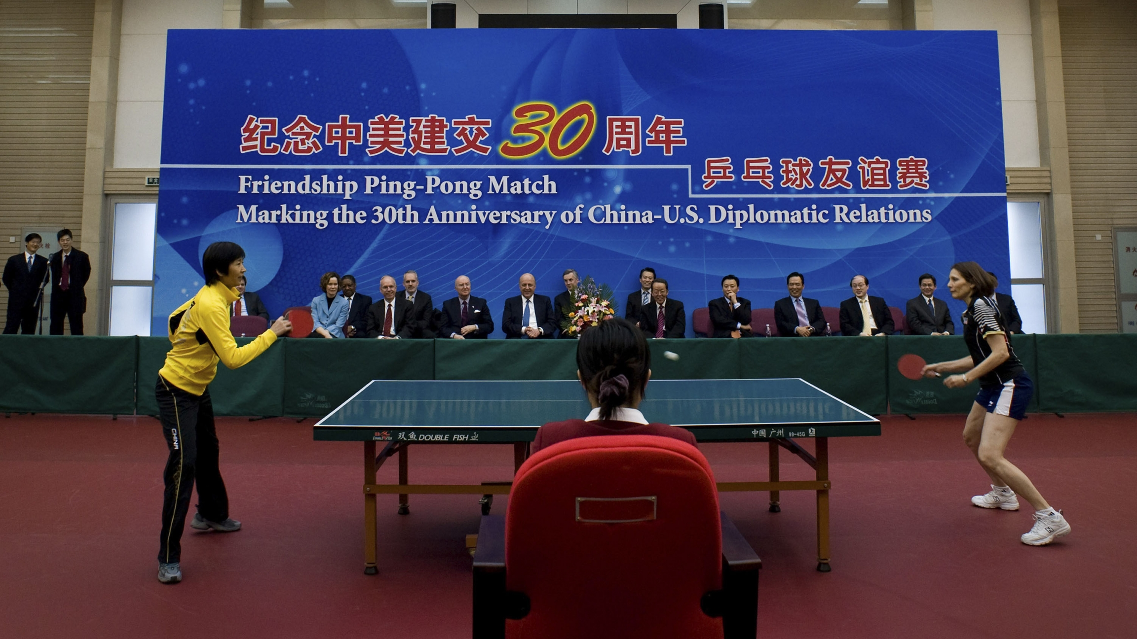 Table top tennis players compete in front of a large blue banner