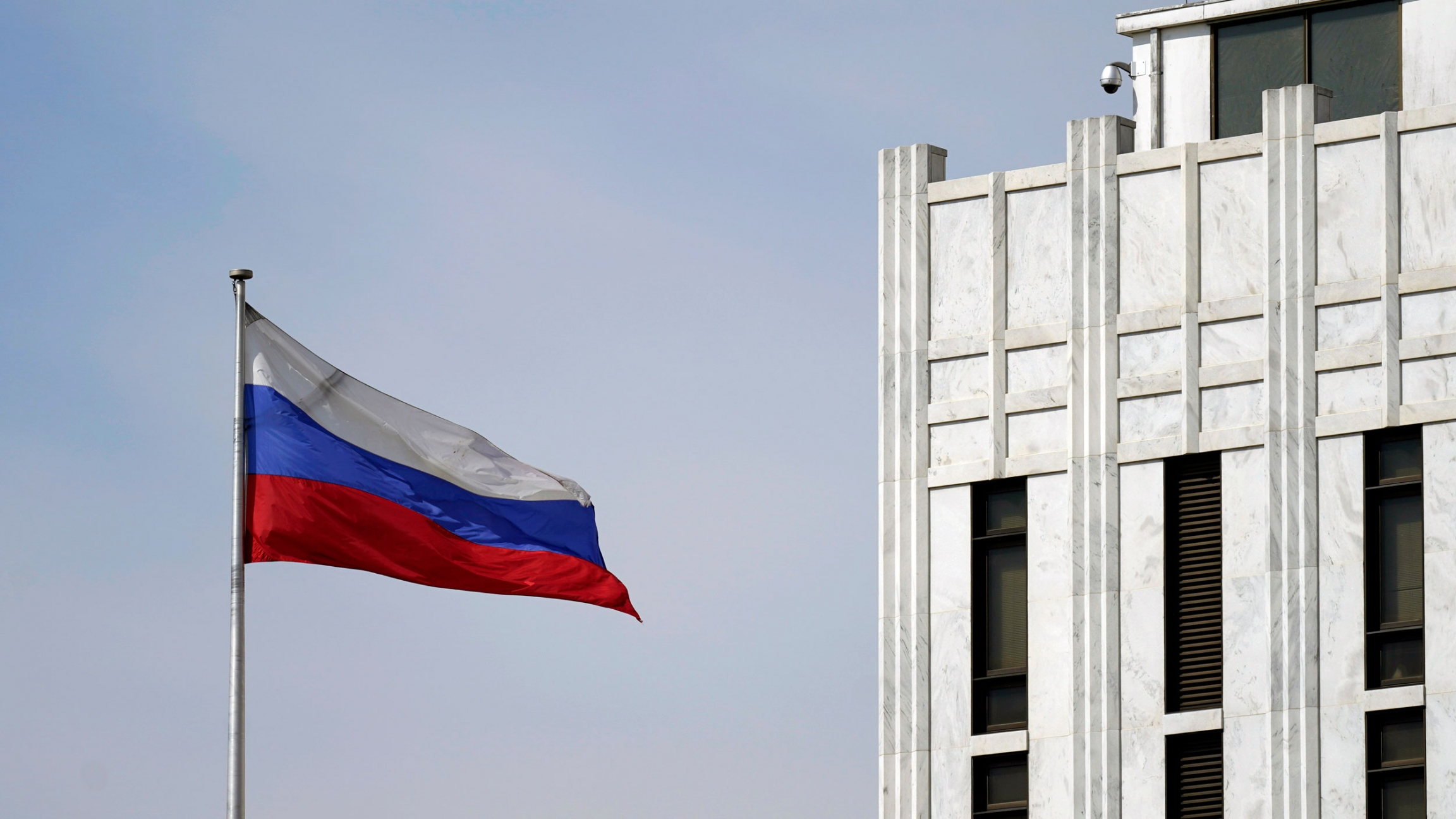 The white, blue and red horizontal stripes of the Russian flag is shown flying in front of the country's embassy building in Washington, DC.