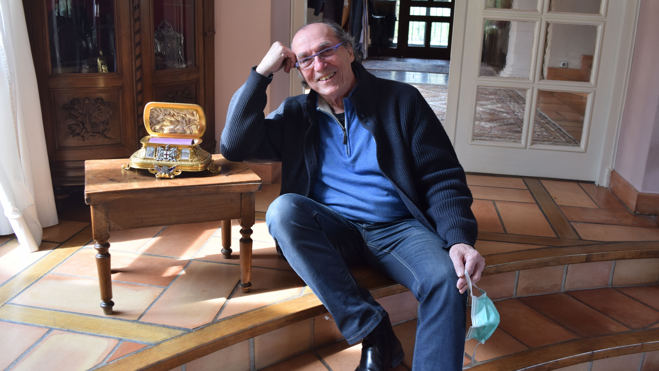 An older white male sits next to a tiny golden casket and smiles