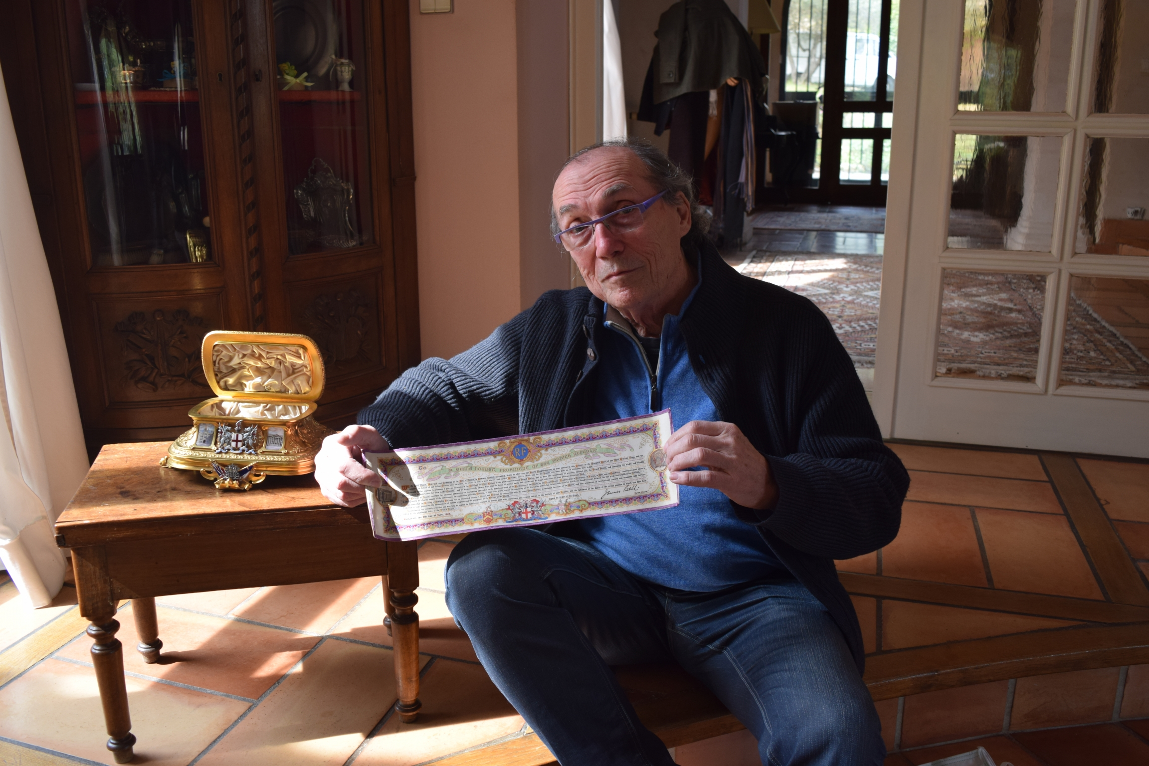"""Michel Becker, art collector, sits with the golden chest featured in the """"The Golden Treasure of the Entente Cordiale."""""""