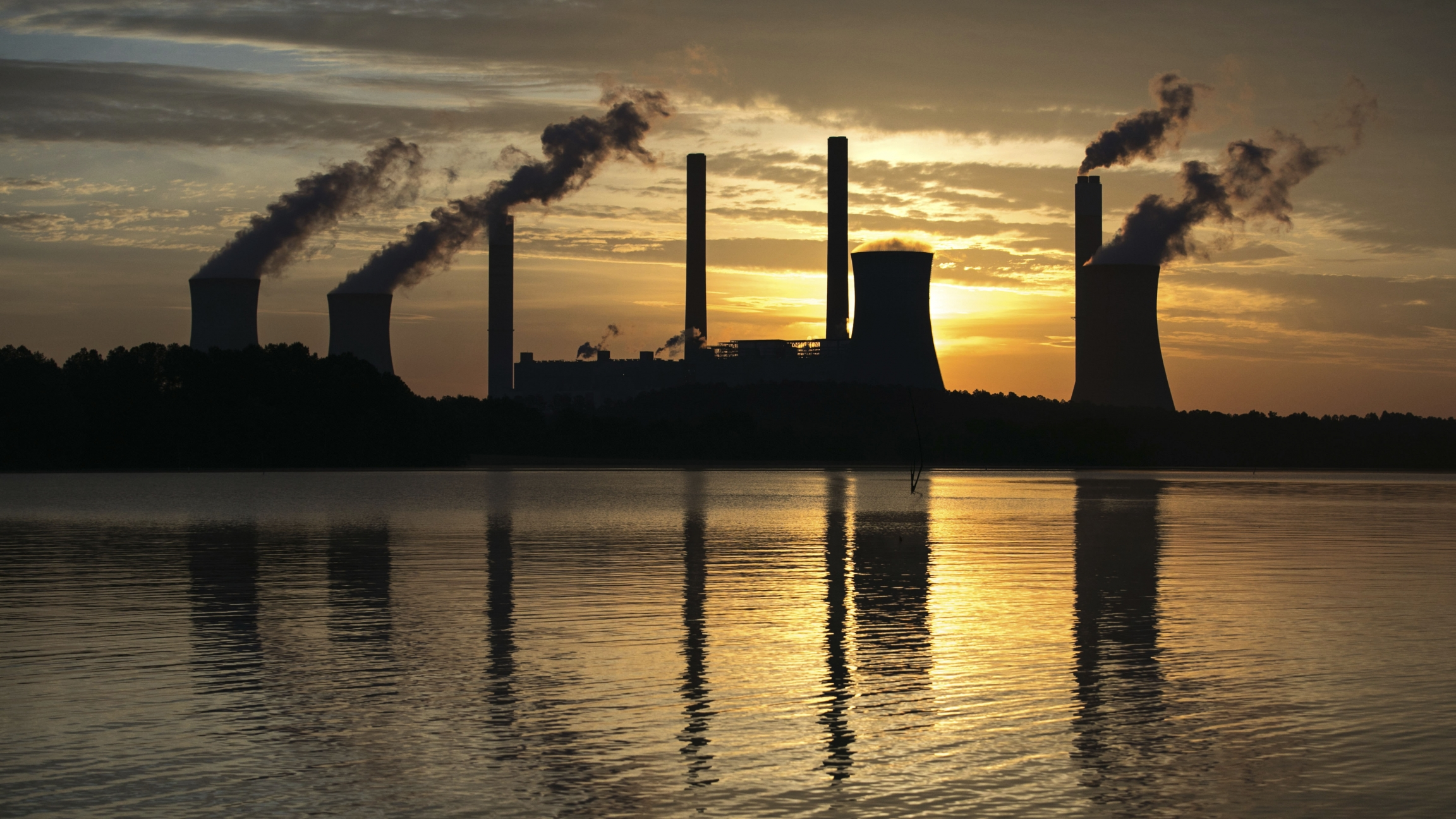 Smoke billows from stacks against a setting sun.