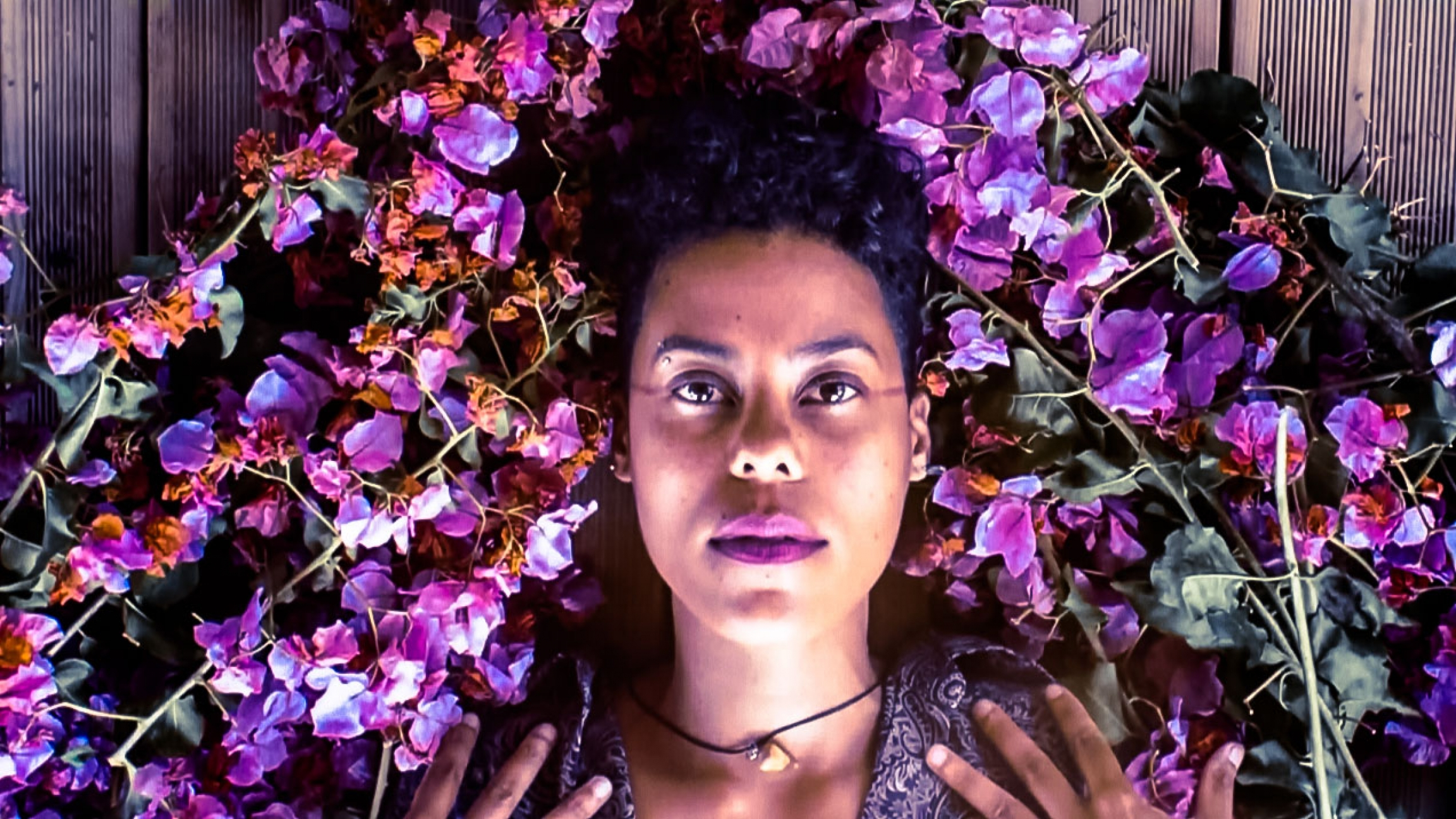 Reunion Island artist Dilo surrounded by pink and magenta flowers around her head.