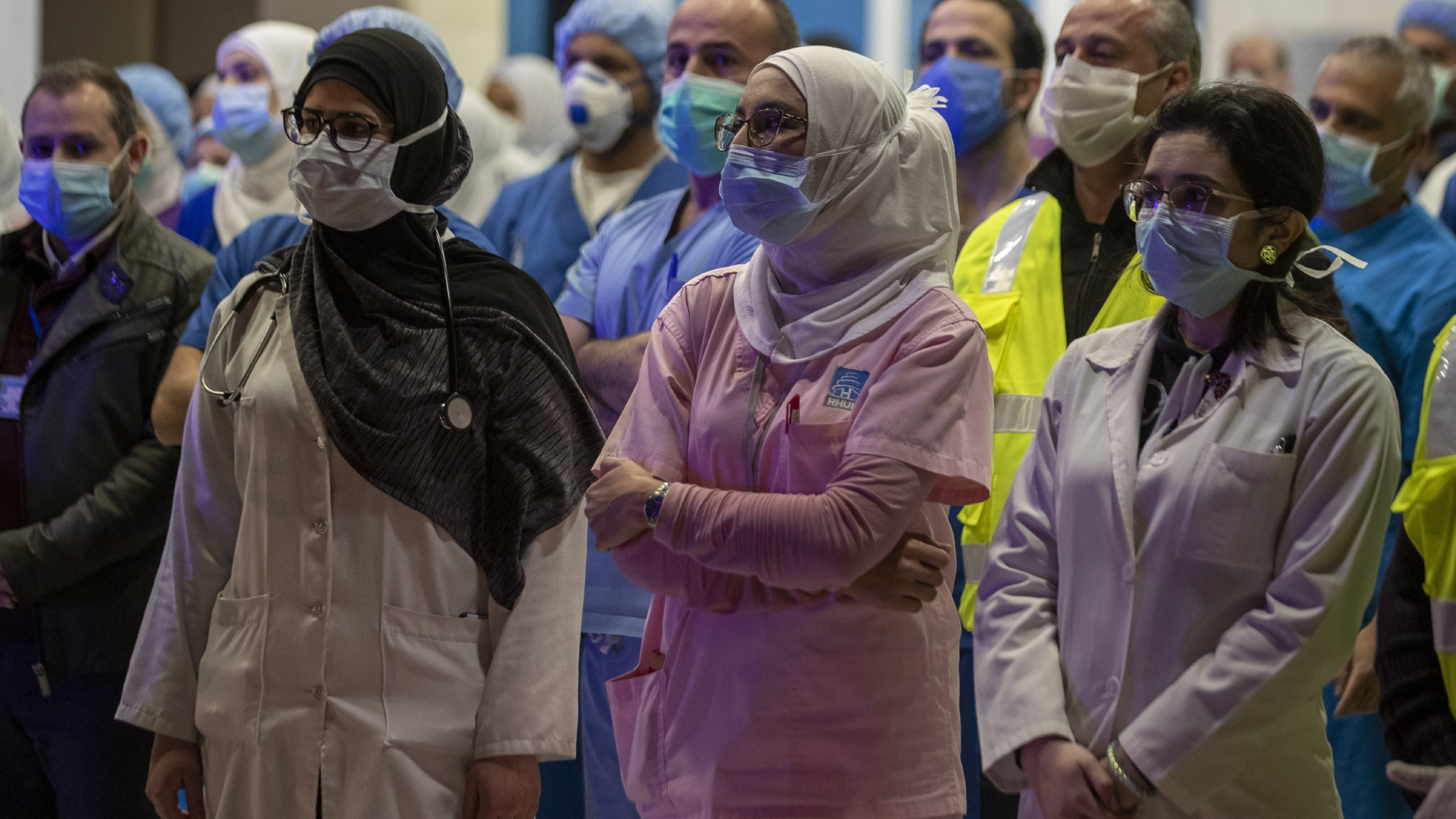Three women health care workers in uniform, wearing headscarves and masks, stand and listen among a crowd of medical workers.