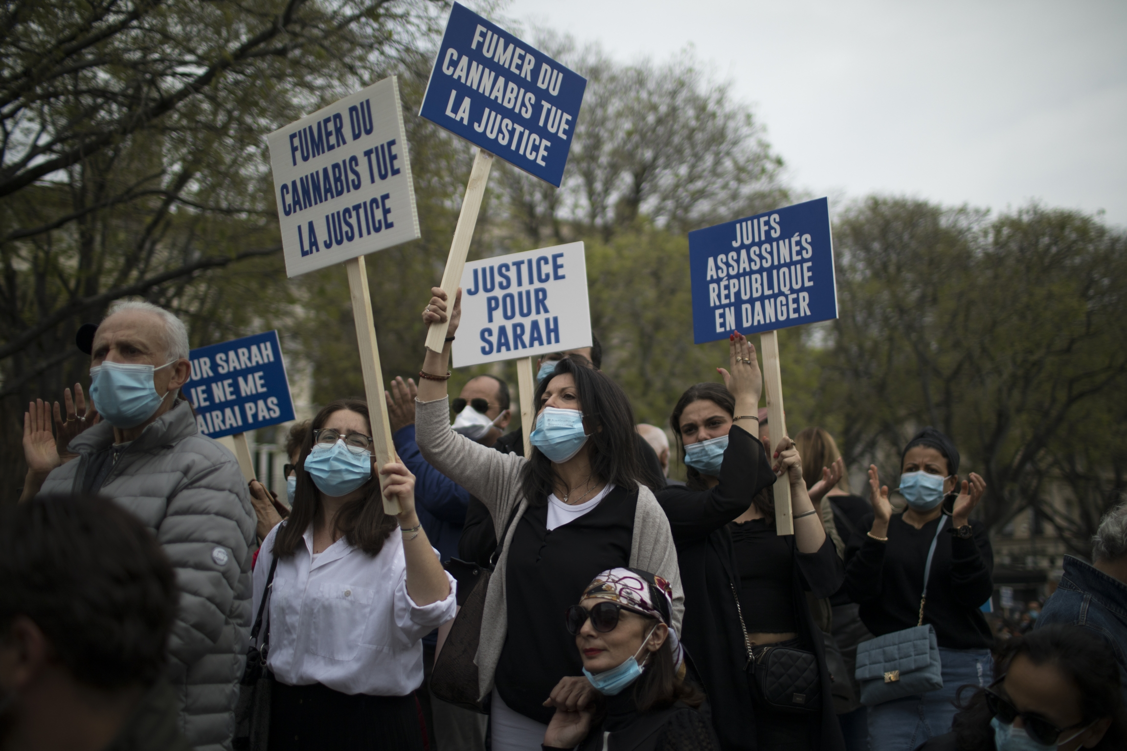 """Protesters hold blue and white signs in French that read """"Justice for Sarah."""""""