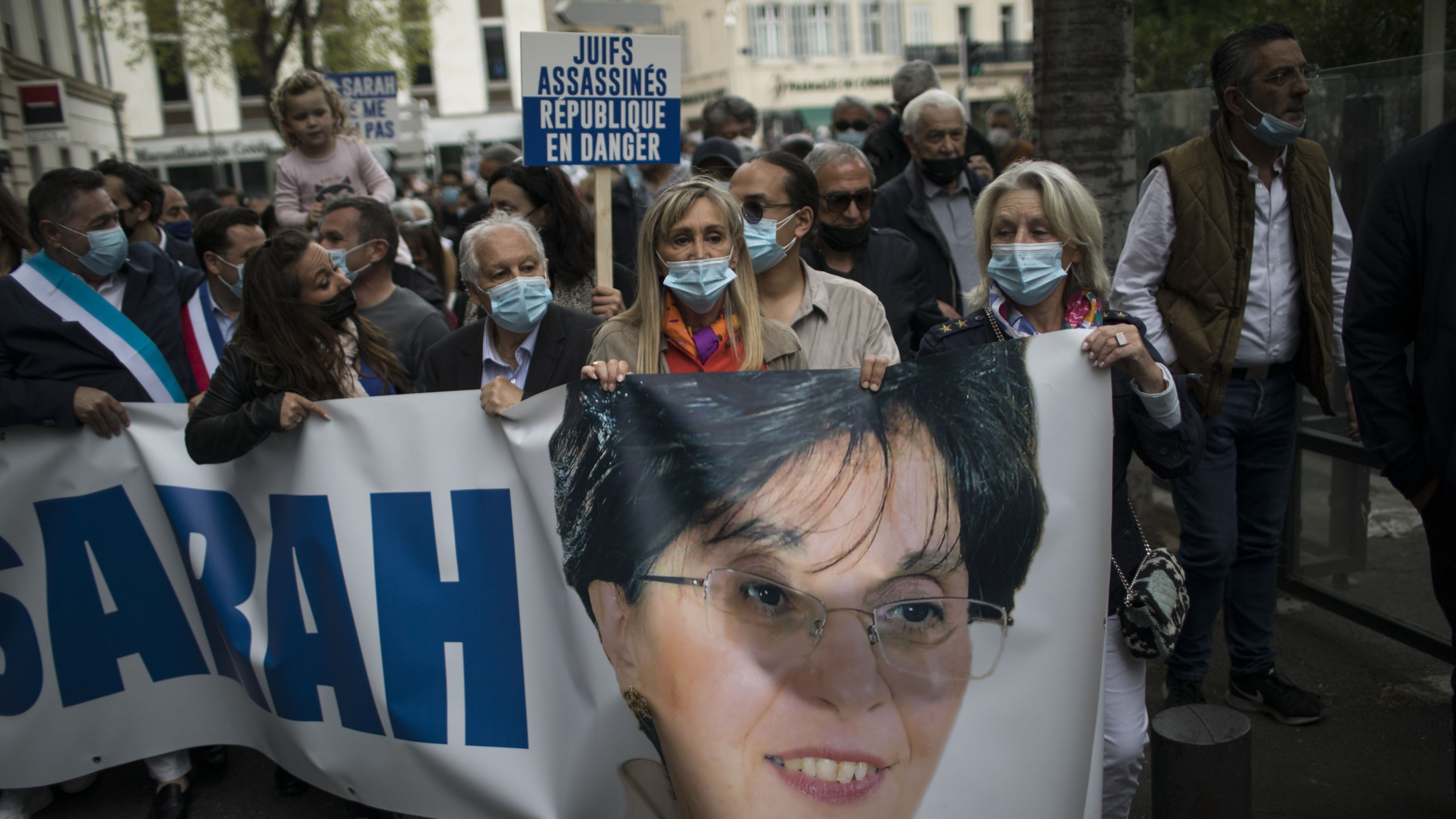 Protesters carry a banner with Sarah Halimi's face and name printed on it in a protest over a court's decision not to try her killer.