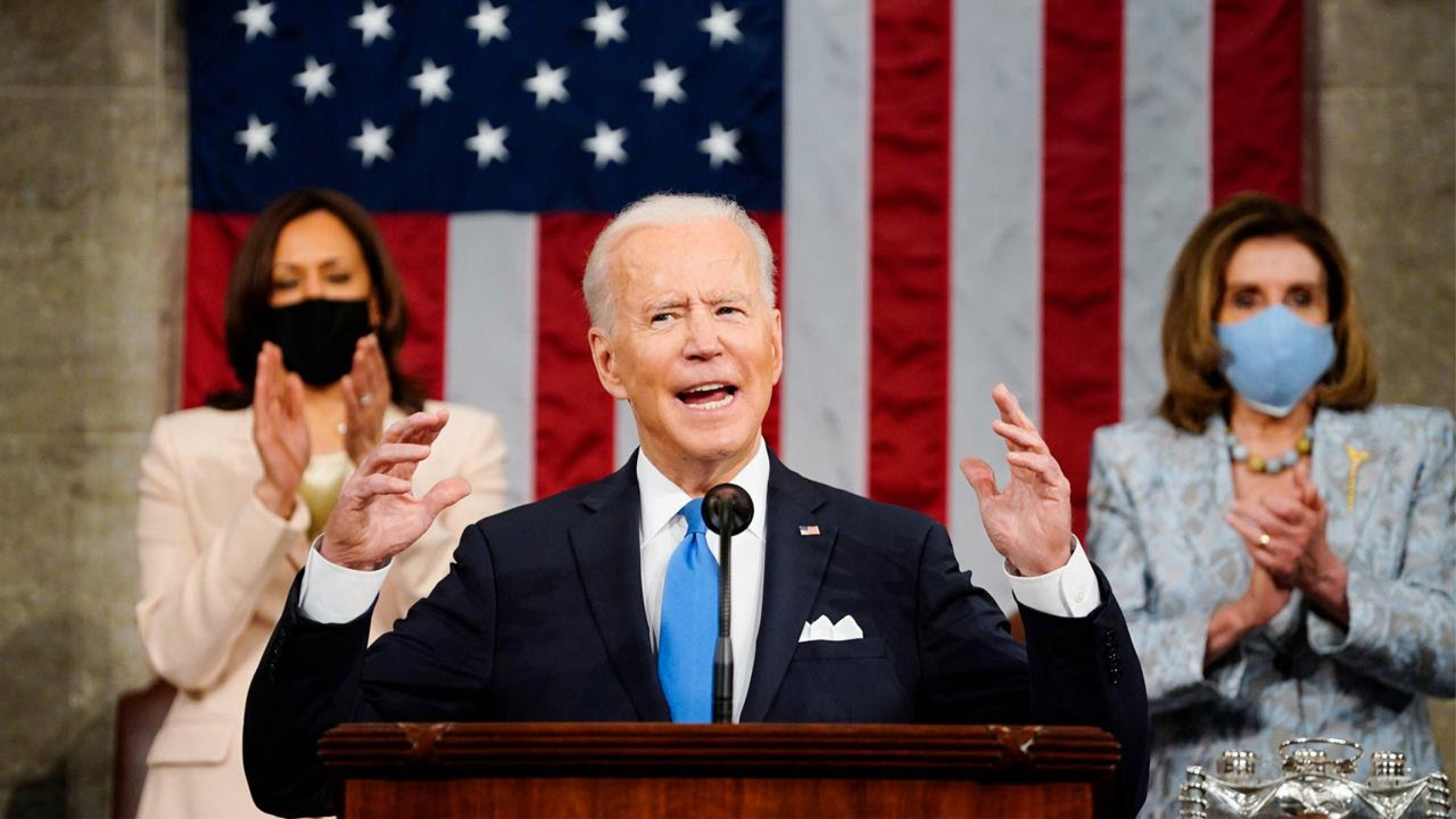 Biden lifts his hands at podium wearing a suit with Harris and Pelosi standing behind him, clapping.
