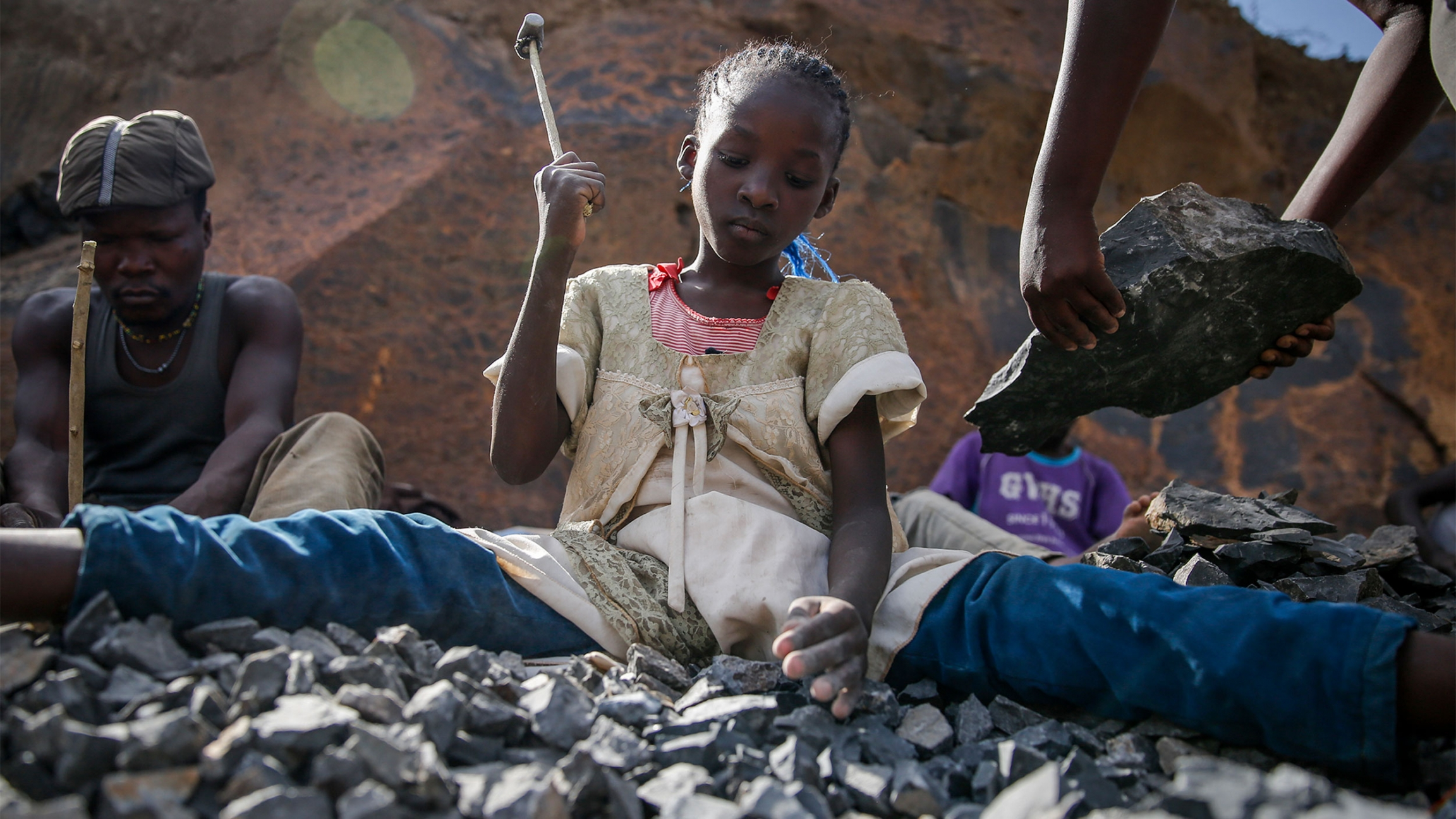 Young girl holds up hammer as she uses it to break rocks in front of her