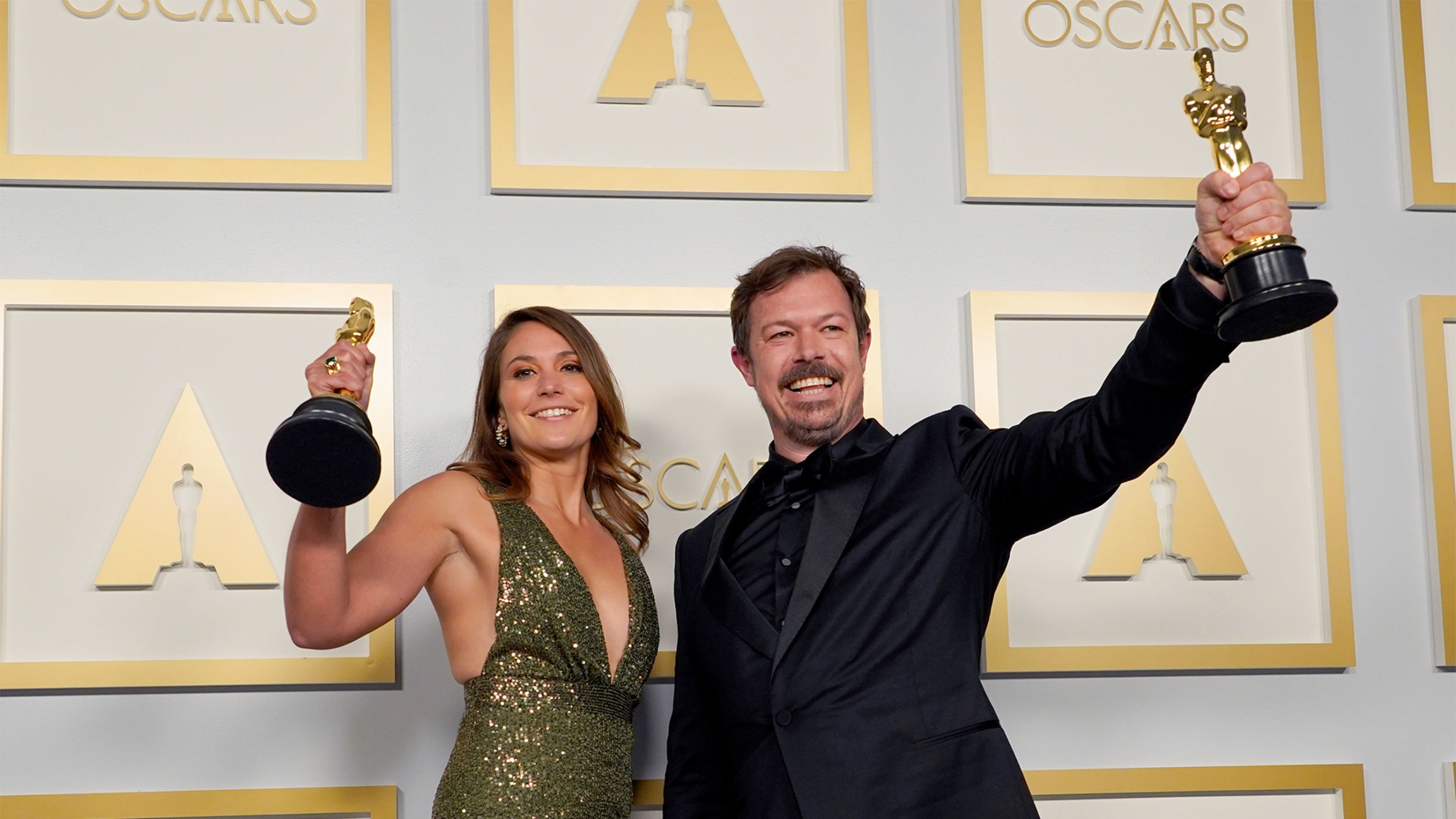 Woman in green dress and man in black suit hold up Oscars