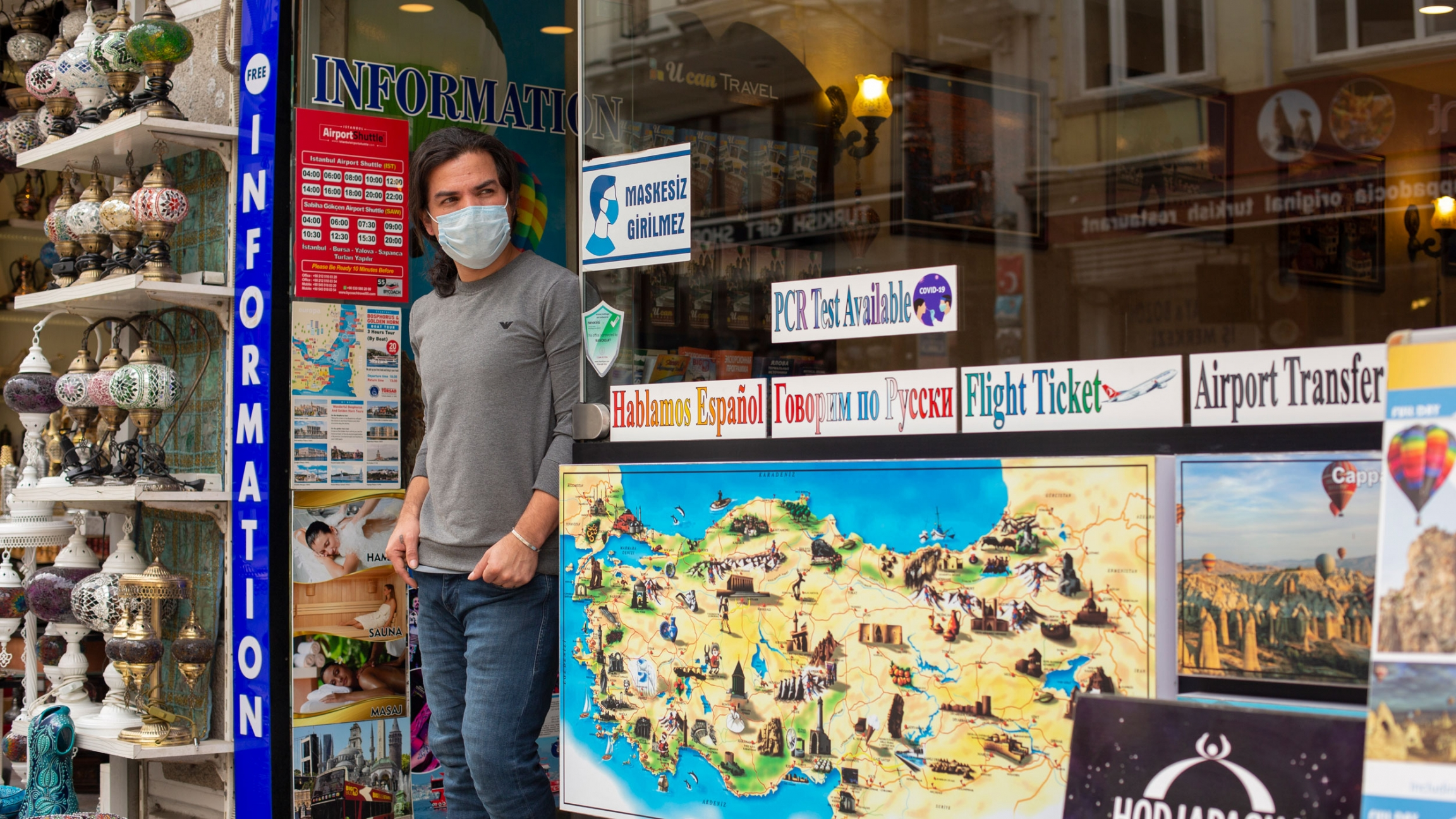 A man is shown wearing a face mask and standing in the doorway of a sightseeing store with maps of Istanbul on the windows.
