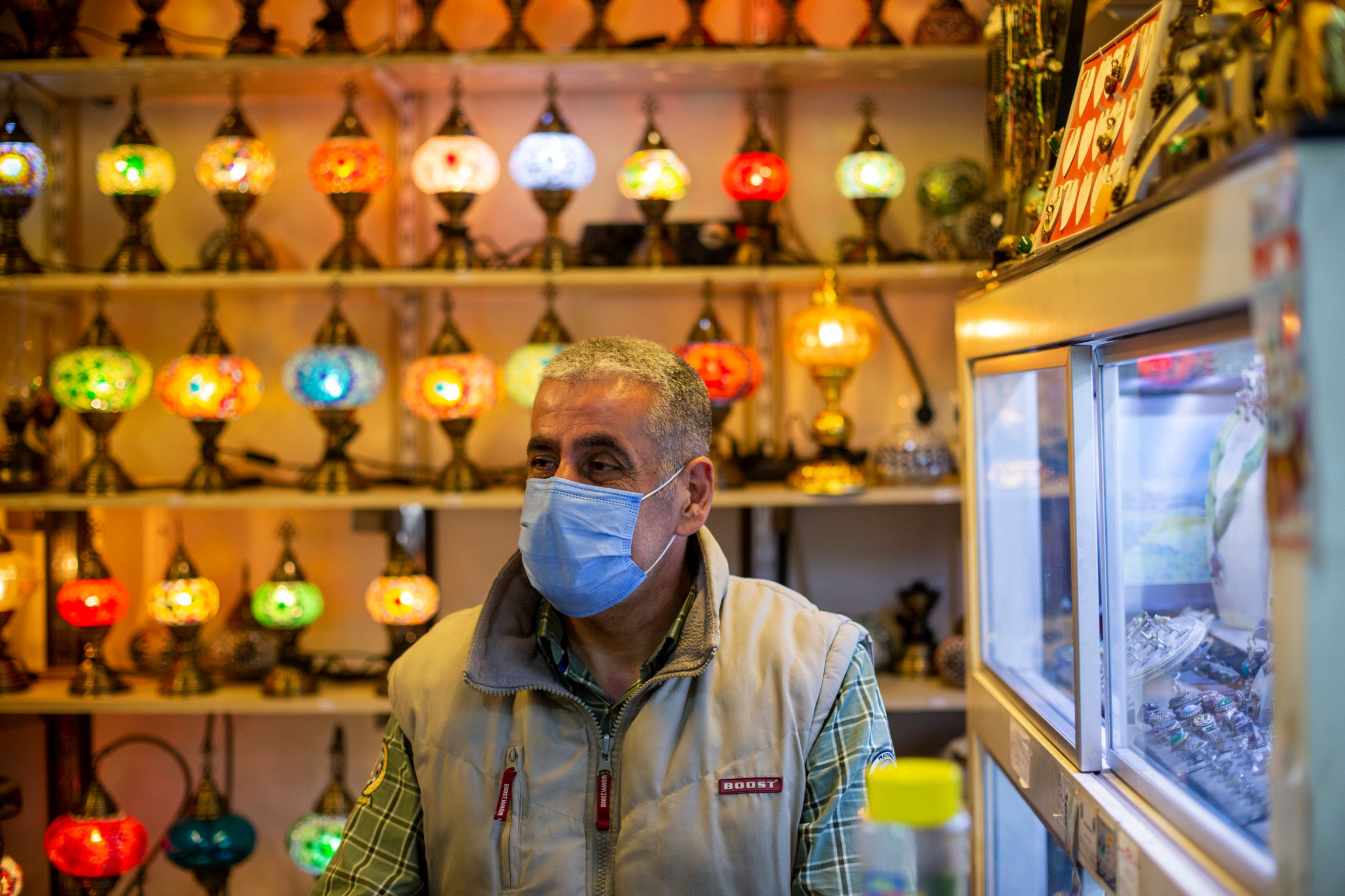 A man is shown with a face mask and standing in front of a wall of brightly colored lamps.