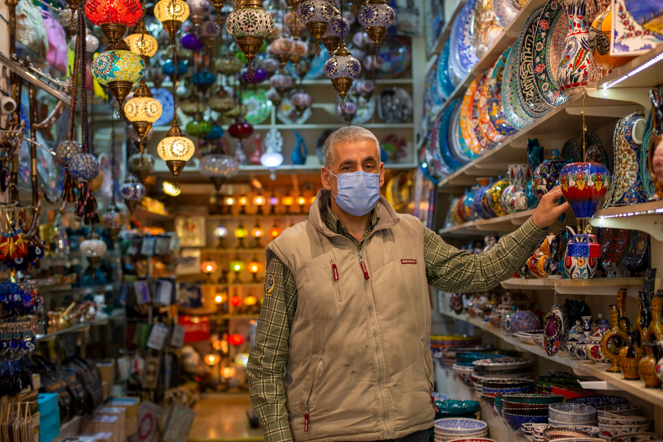 A man is shown wearing a face mask and khaki vest while standing in an aisle with colorful lamps.