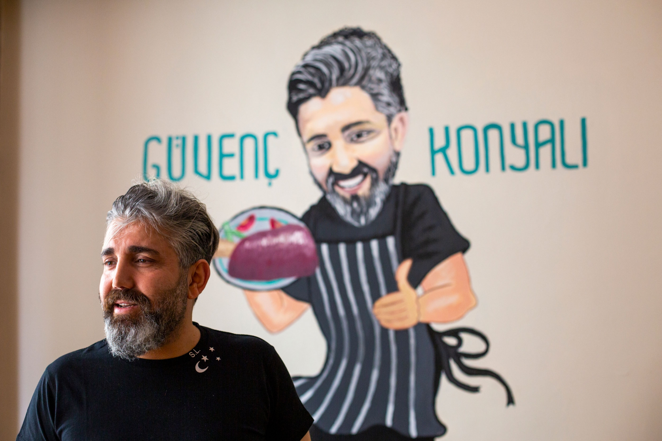 A man is shown with a salt and pepper beard and wearing a black shirt with an illustration of a chef behind him.