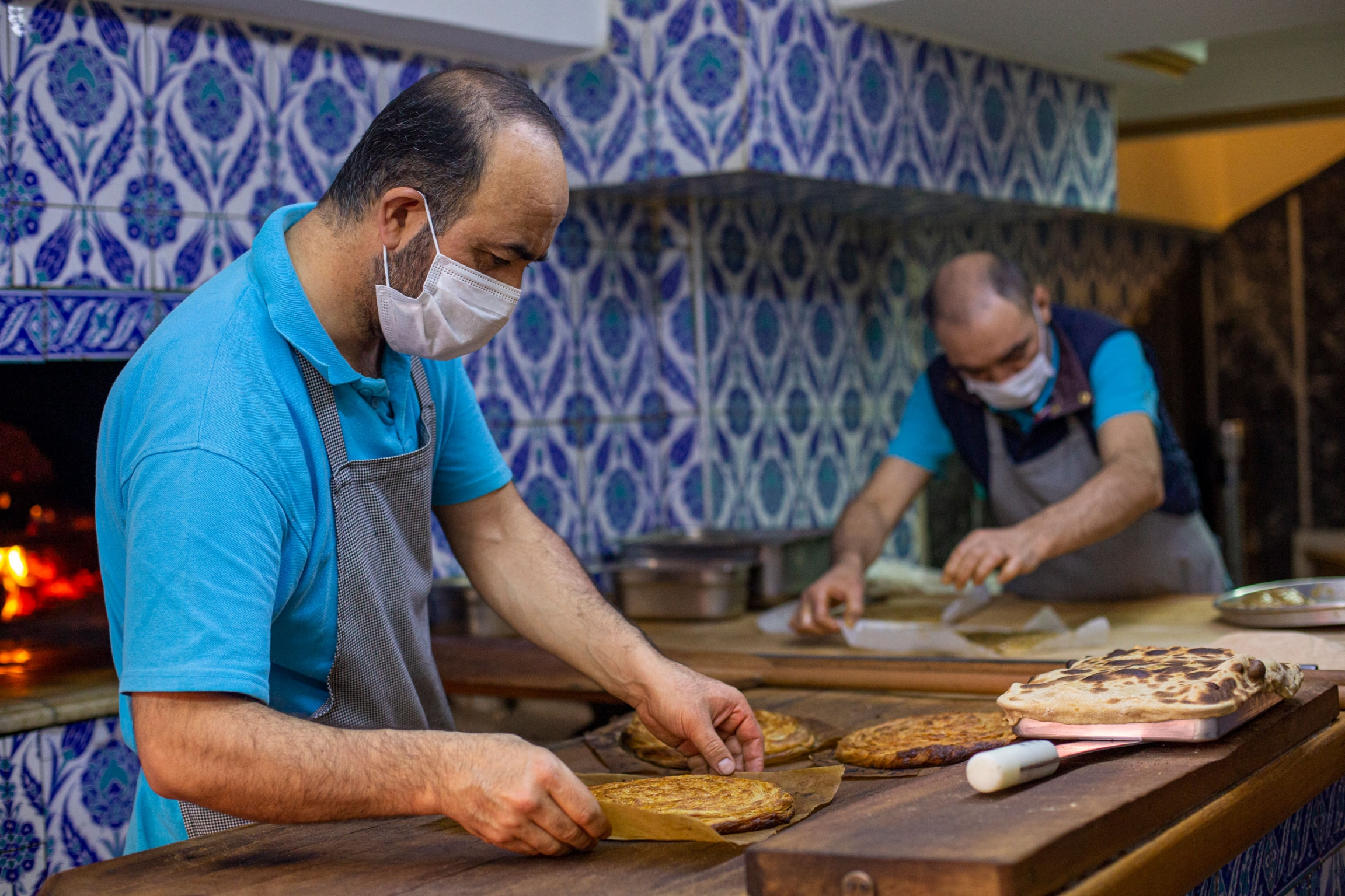 A man is shown wearing a blue shirt and gray aprin while handling a flat bread-like dish.