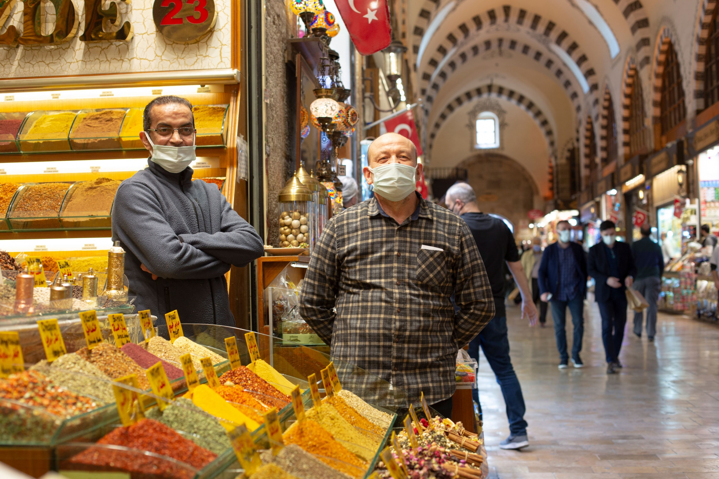 Two men are shown wearing face masks and standing next to a large display of sweets.