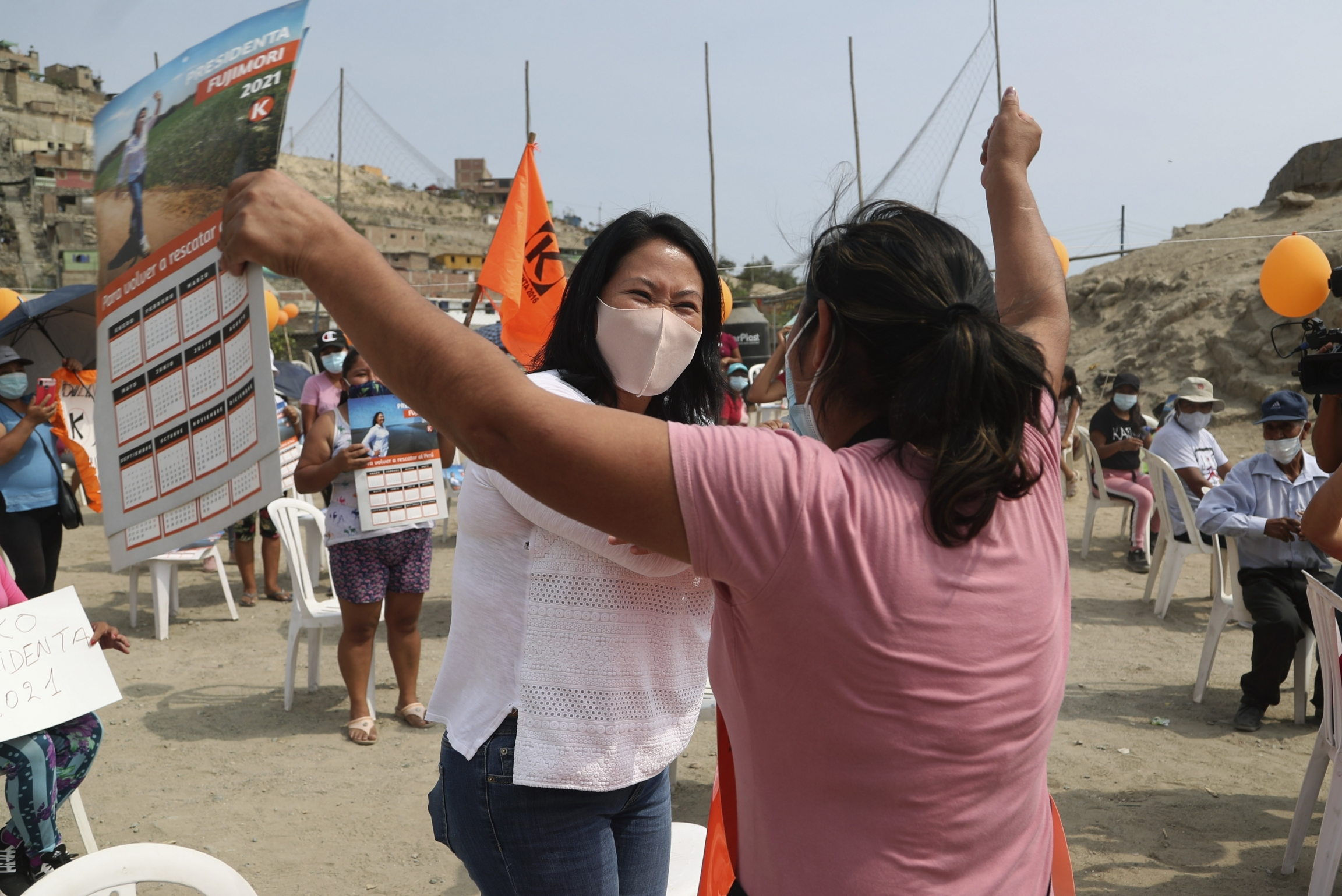 Wearing a mask to curb the spread of the new coronavirus, presidential candidate and daughter of imprisoned ex-President Alberto Fujimori, Keiko Fujimori, of the Popular Force party, greets a supporter as she campaigns in San Juan de Lurigancho on the out