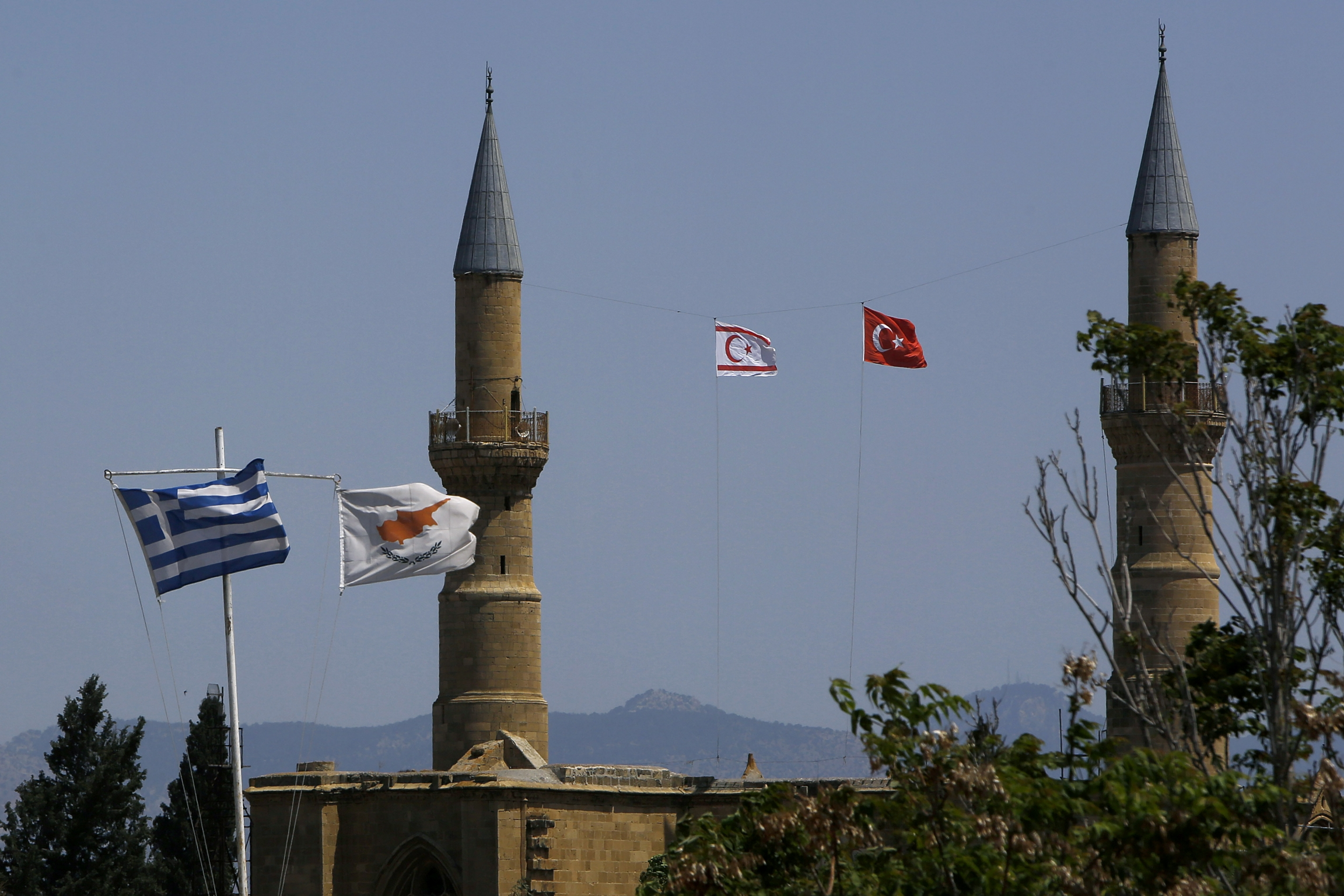 Greek and Cypriot flags flutter on poles on the left, as Turkish and Turkish Cypriot breakaway flags fly between minarets on the right