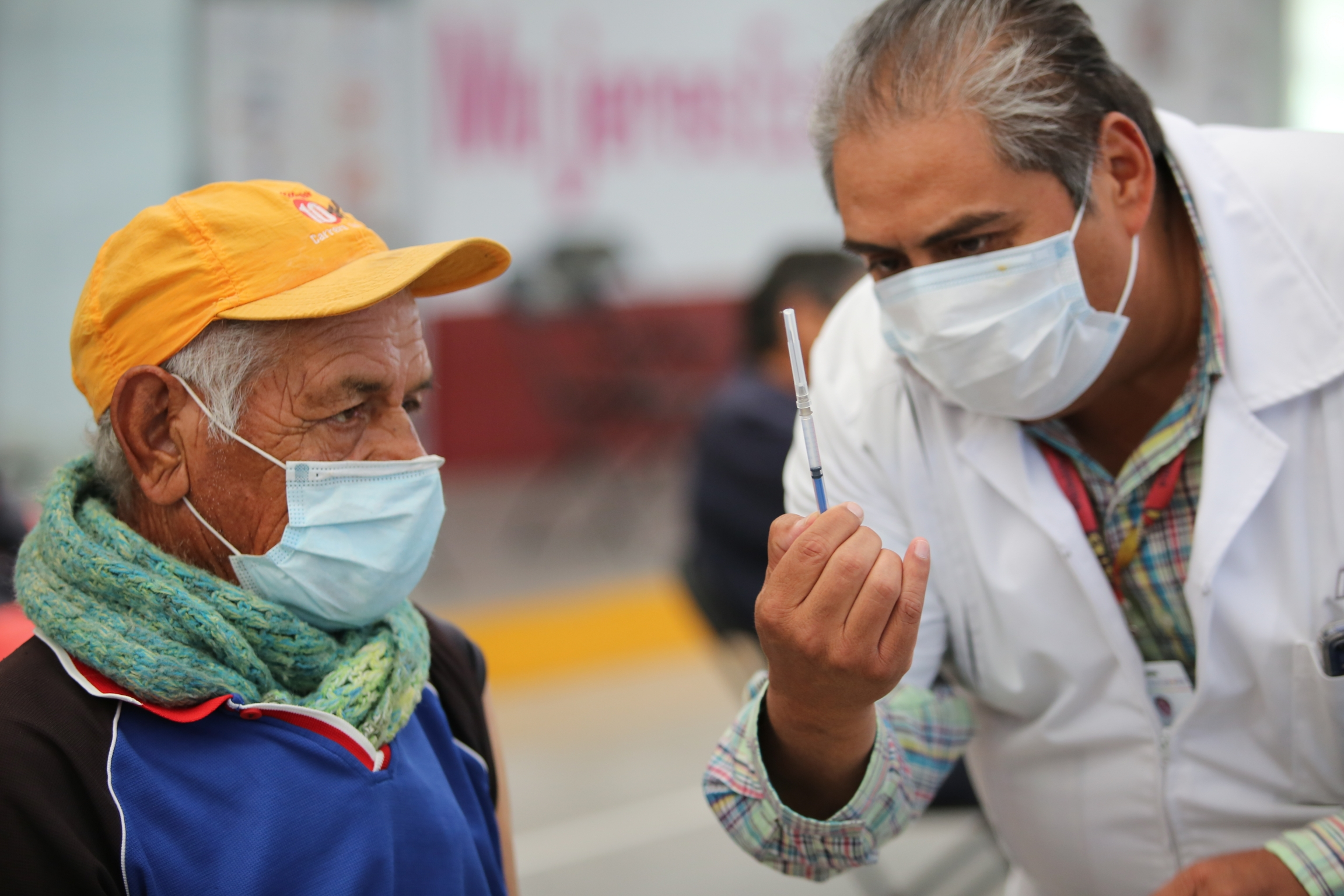 A nurse shows an elderly man a syringe prepared with a dose of the Sinovac COVID-19 vaccine, before he is inoculated at the Americas Cultural Center in Ecatepec, Mexico, April 3, 2021.