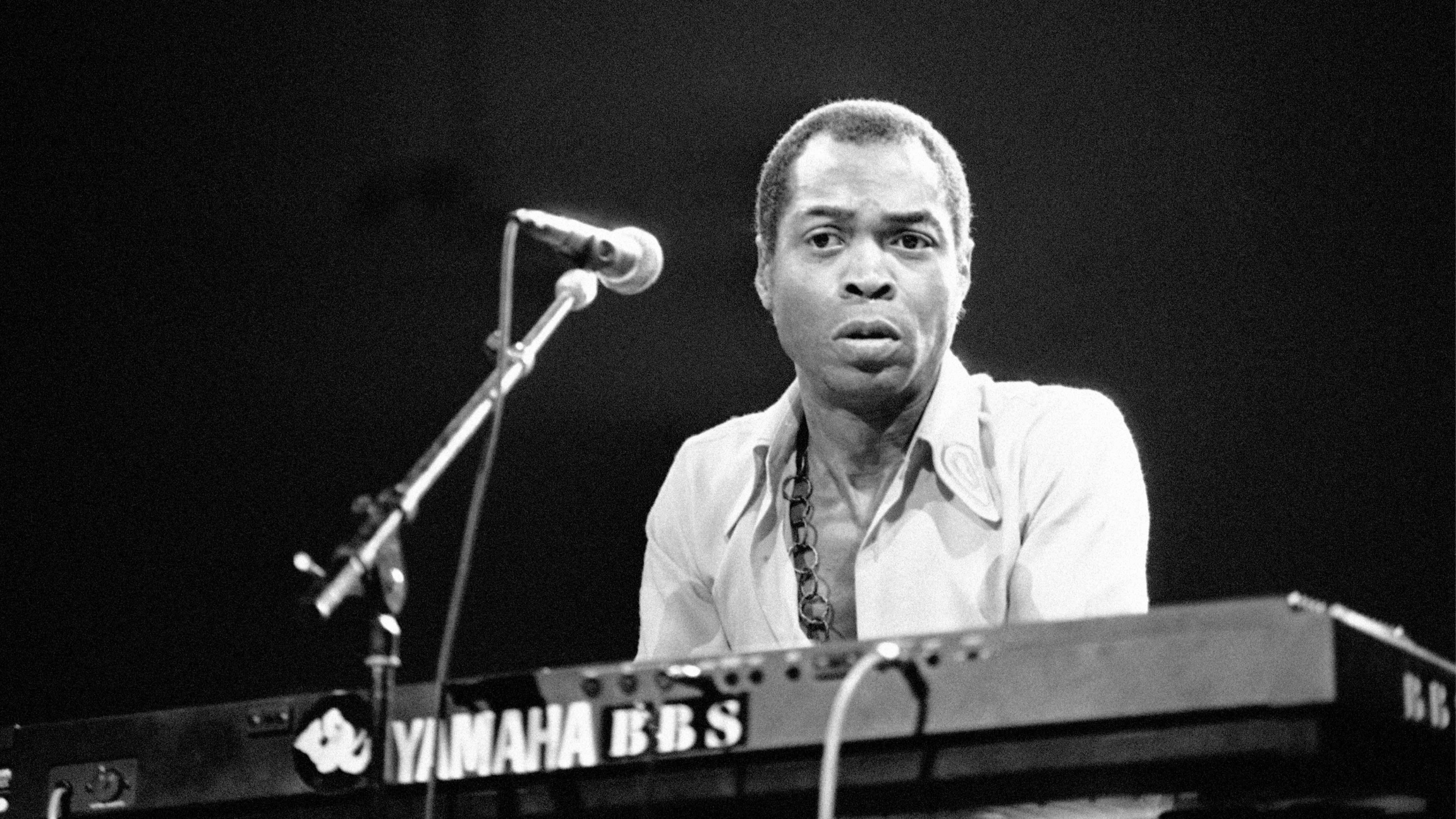 Fela Kuti is shown playing an electric keyboard and standing behind a microphone.