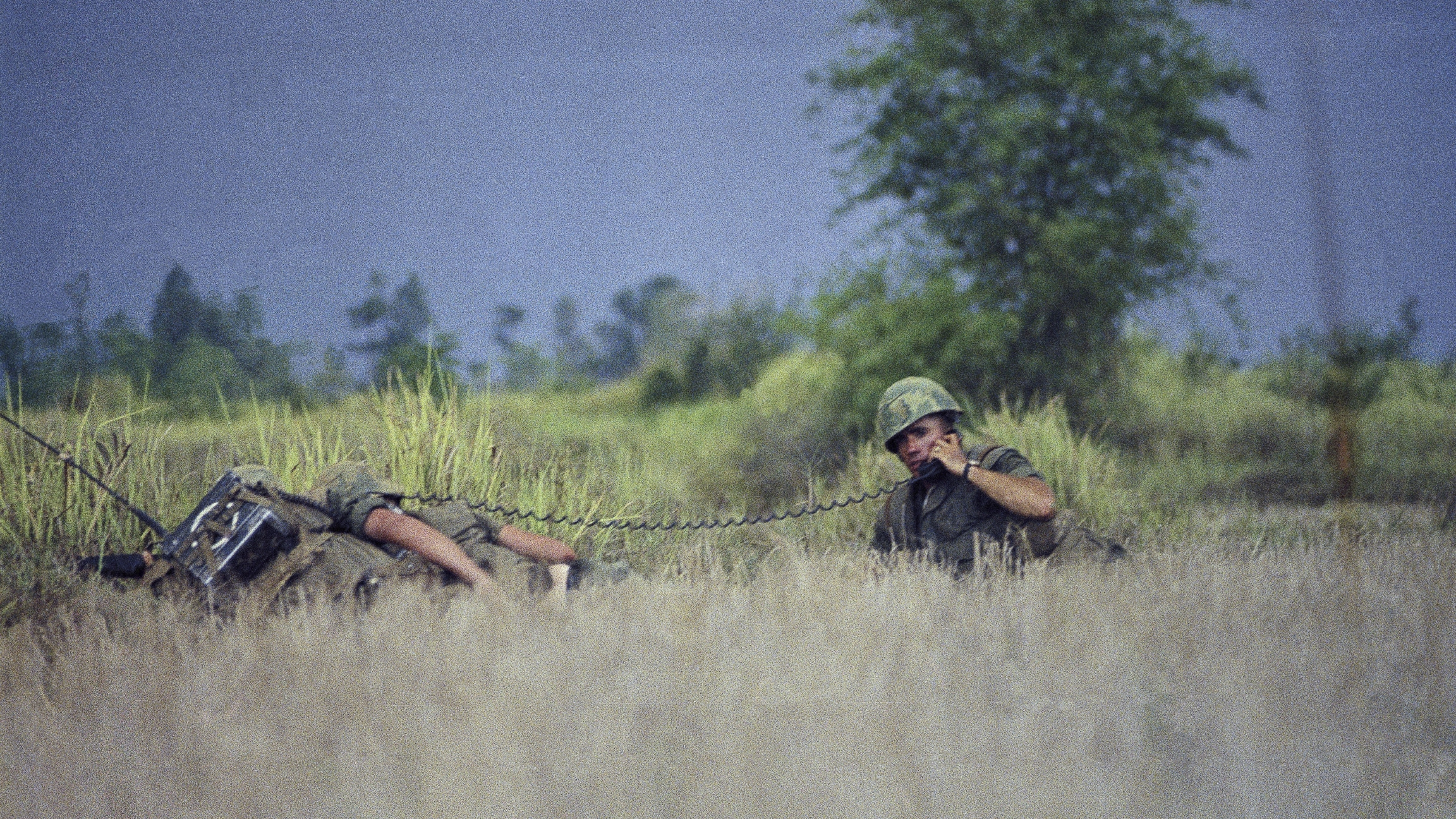 Two men in camouflage carry guns in a rice paddy in Vietnam.