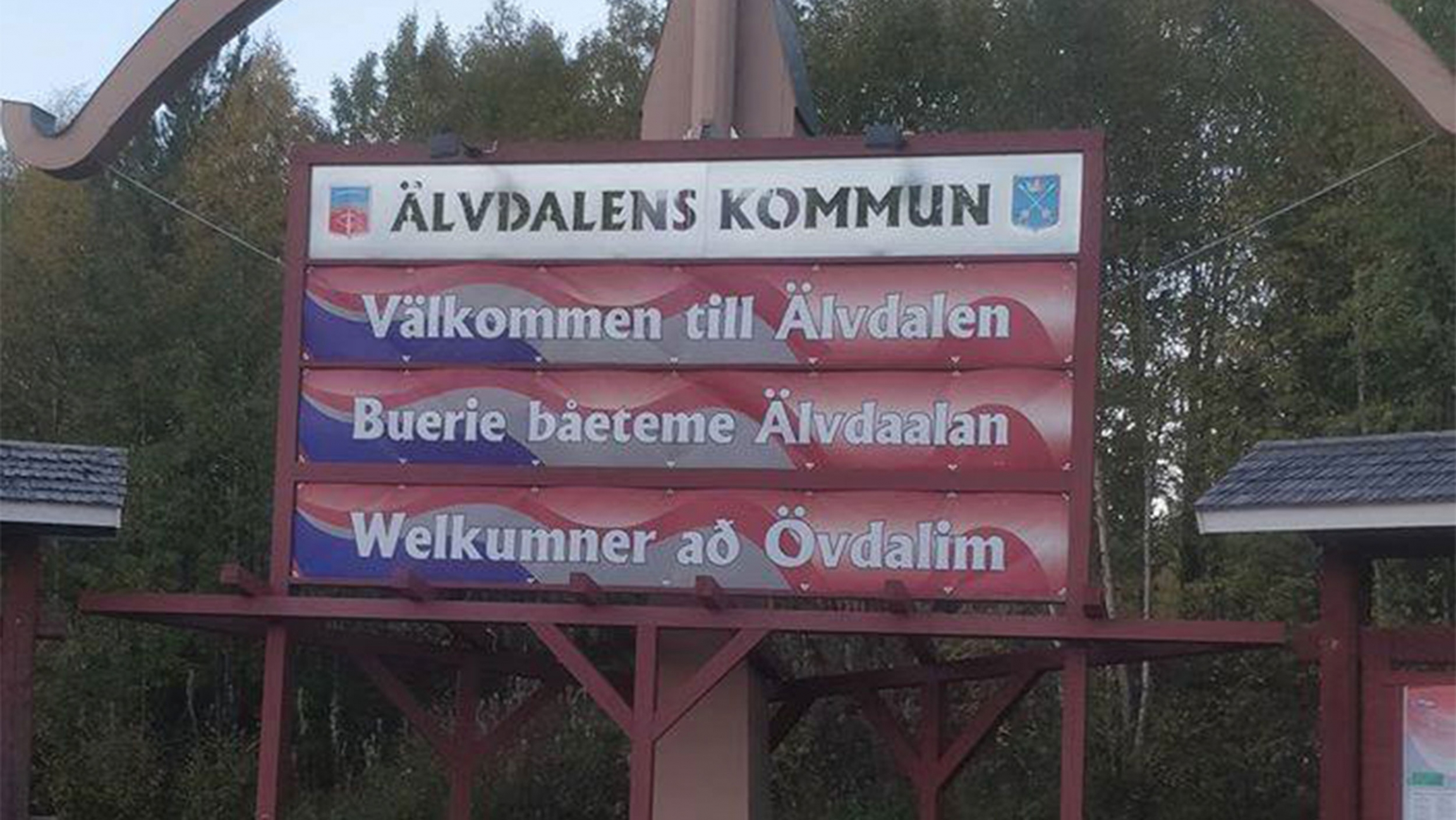 """A red and white sign that says """"Welcome to Älvdalen"""" in the language Elfdalian"""