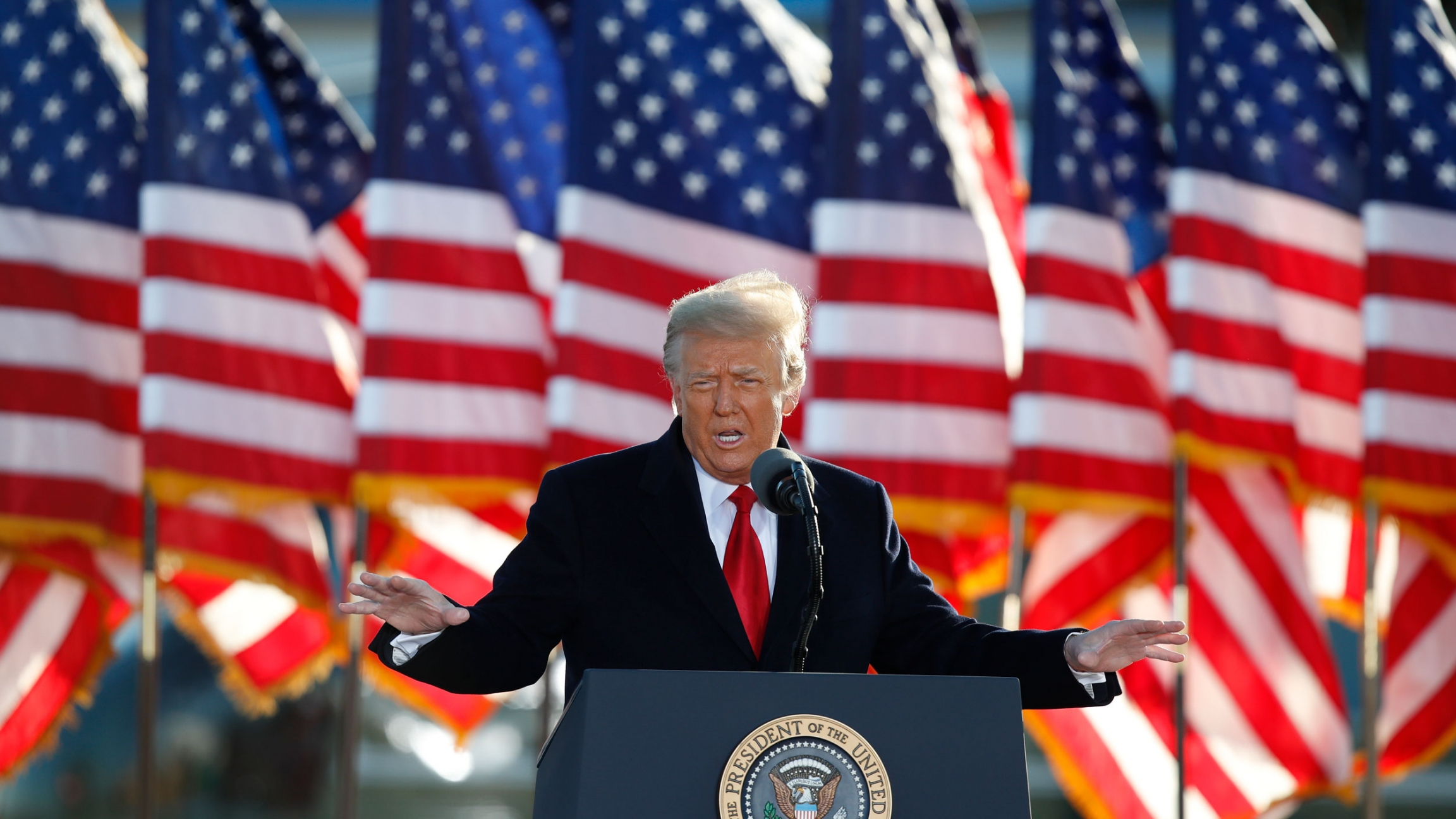 Donald Trump is shown wearing a dark suit overcoat and red tie with several US flags in the background.