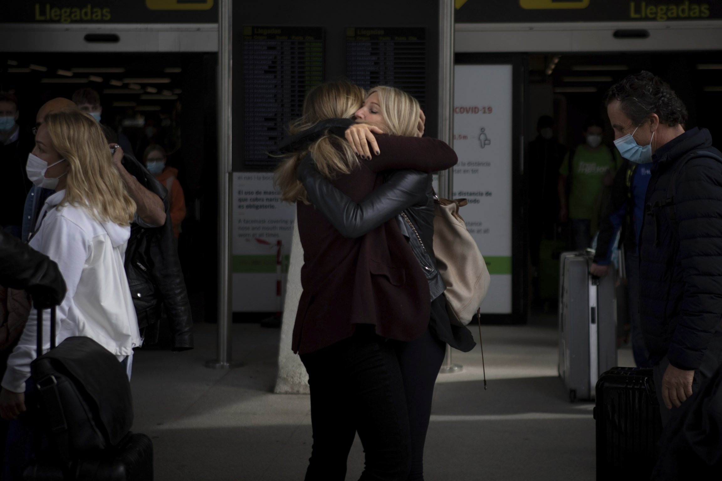 Two women in black clothing embrace in an airport