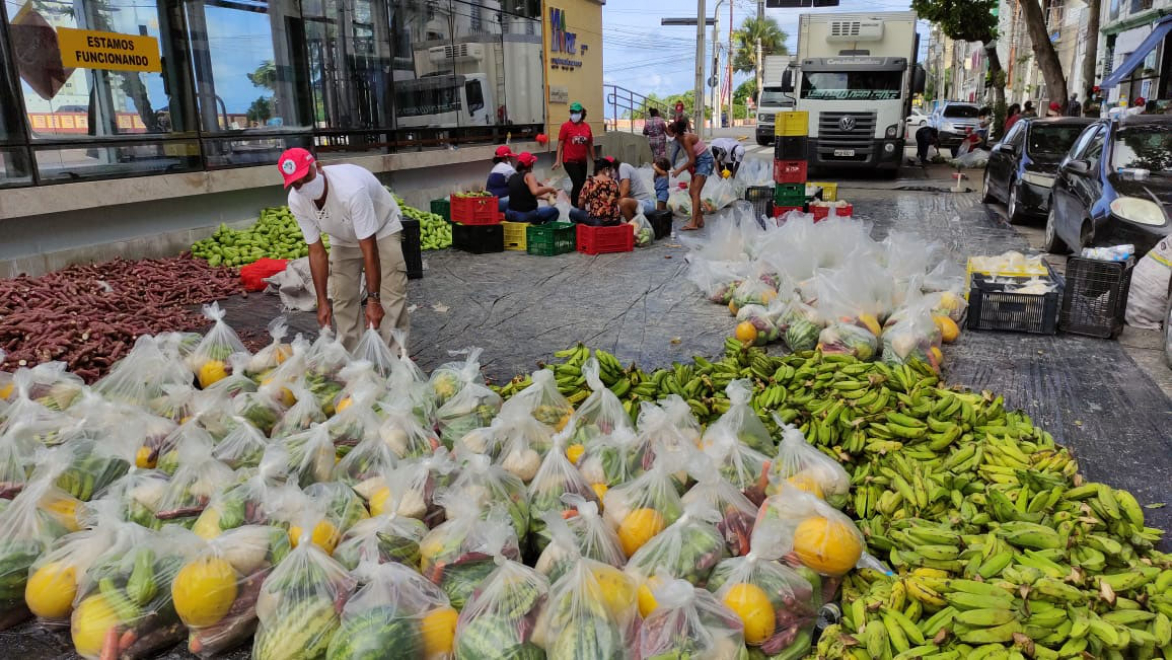 A man stands near lots of bags of watermelons