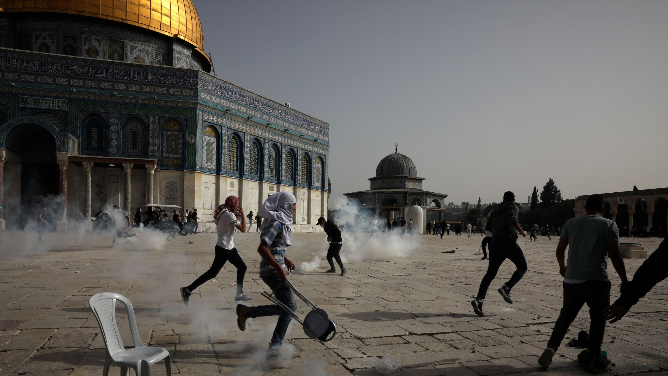 Palestinians run away from tear gas during clashes with Israeli security forces at the Al-Aqsa Mosque compound in Jerusalem's Old City Monday, May 10, 2021.