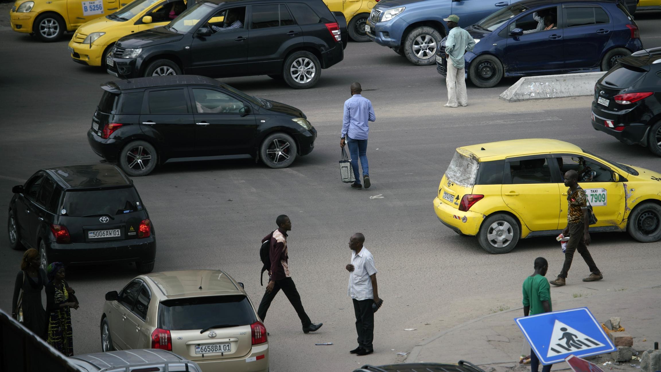 Pedestrians cross a busy street in Kinshasa.