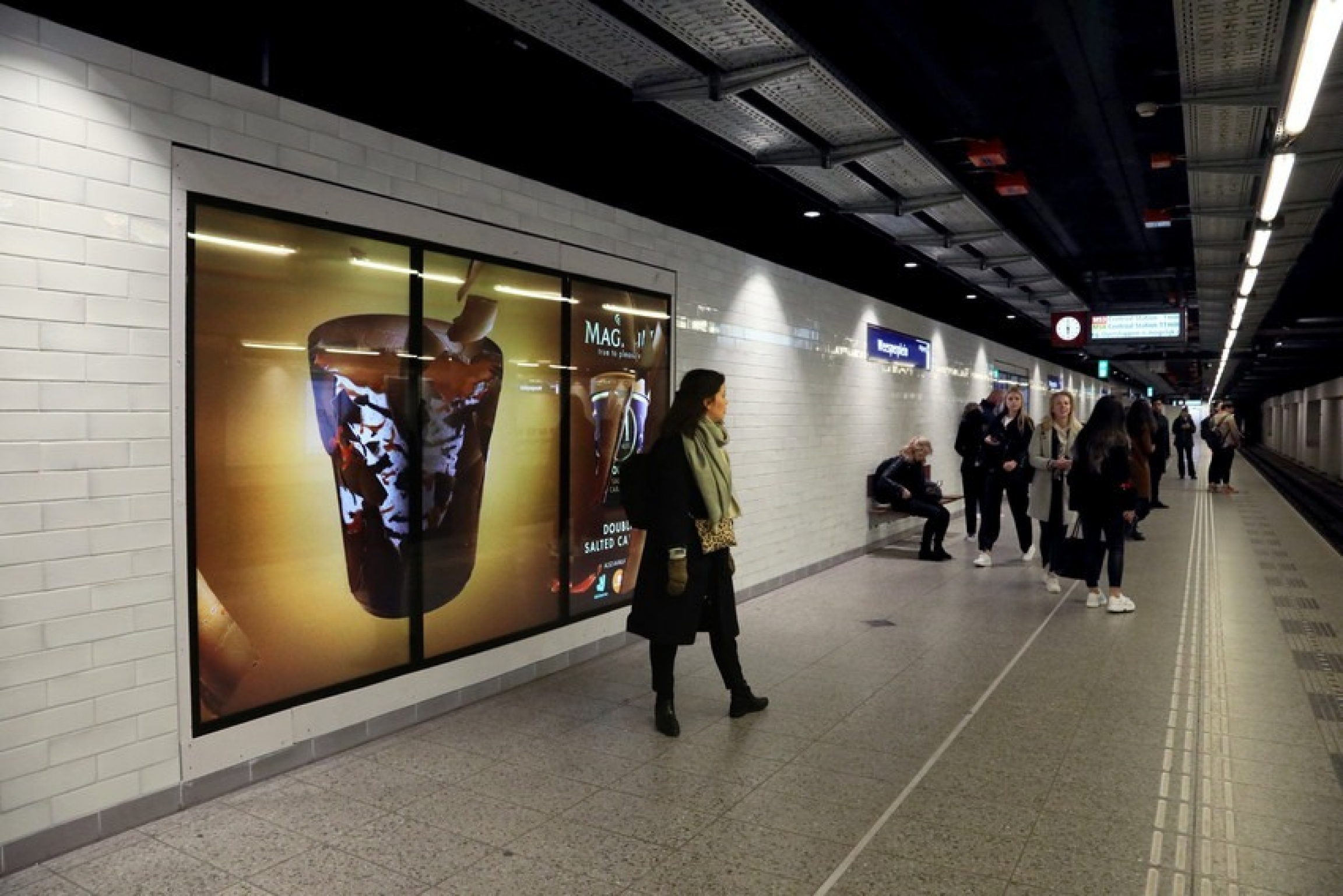 An ad for an ice cream pint glows in an Amsterdam metro.