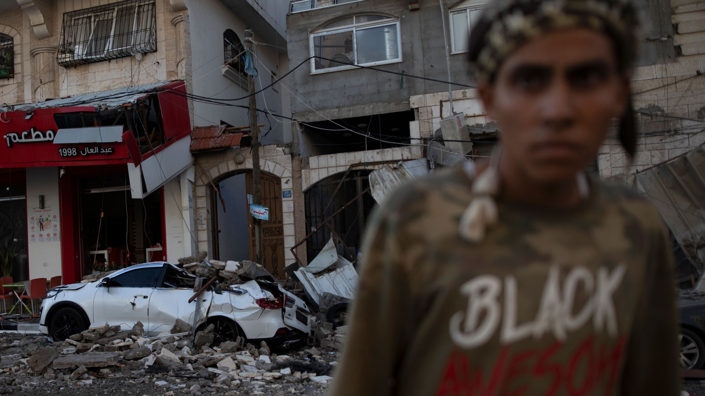 """A person is shown in soft focus wearing a shirt with the word """"Black"""" printed on it with the rubble of a bombed building a car in the background."""