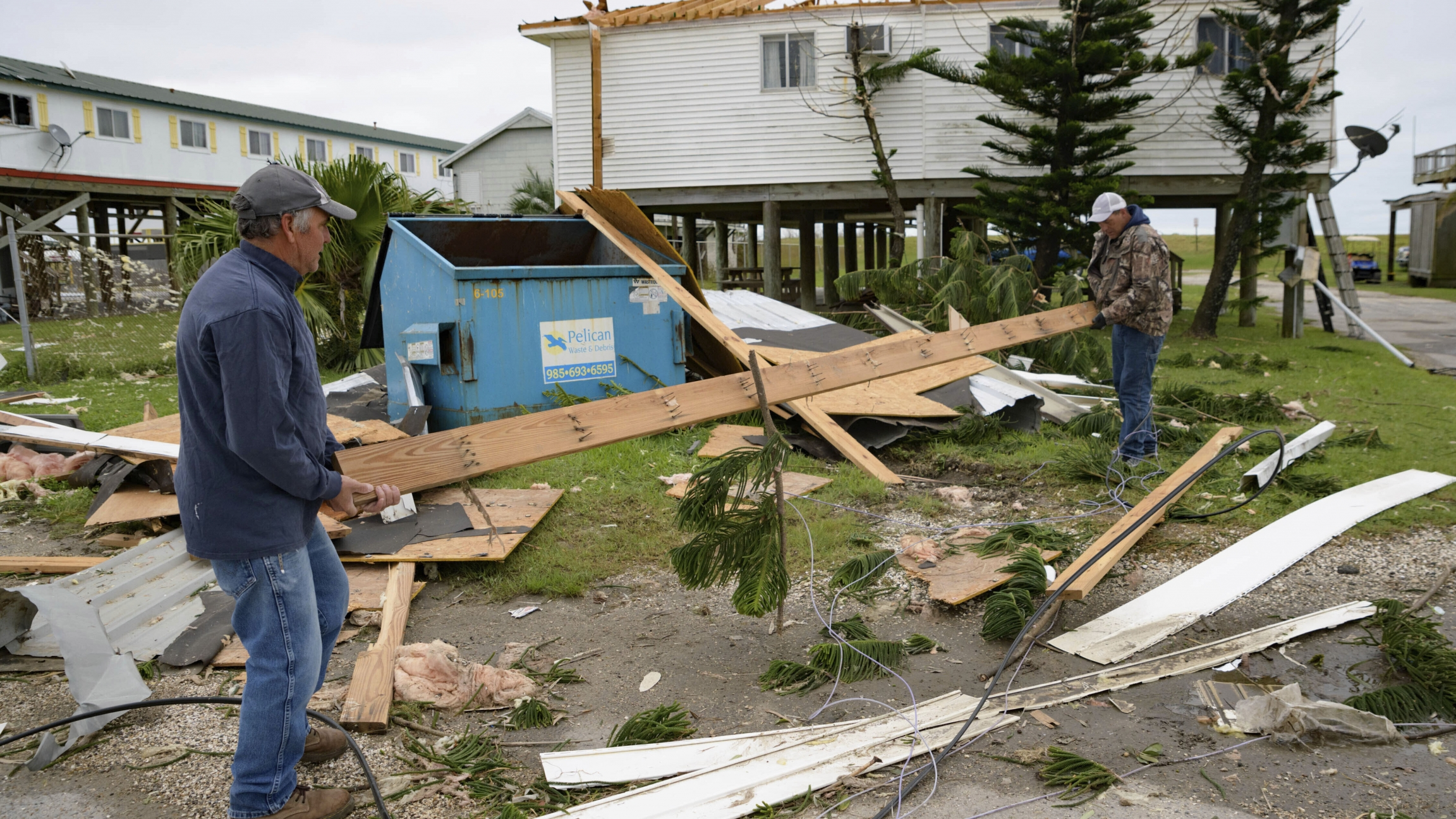 In this Oct. 30, 2020, file photo, Mark Andollina, left, and Shane Holder, remove part of a roof damaged by Hurricane Zeta