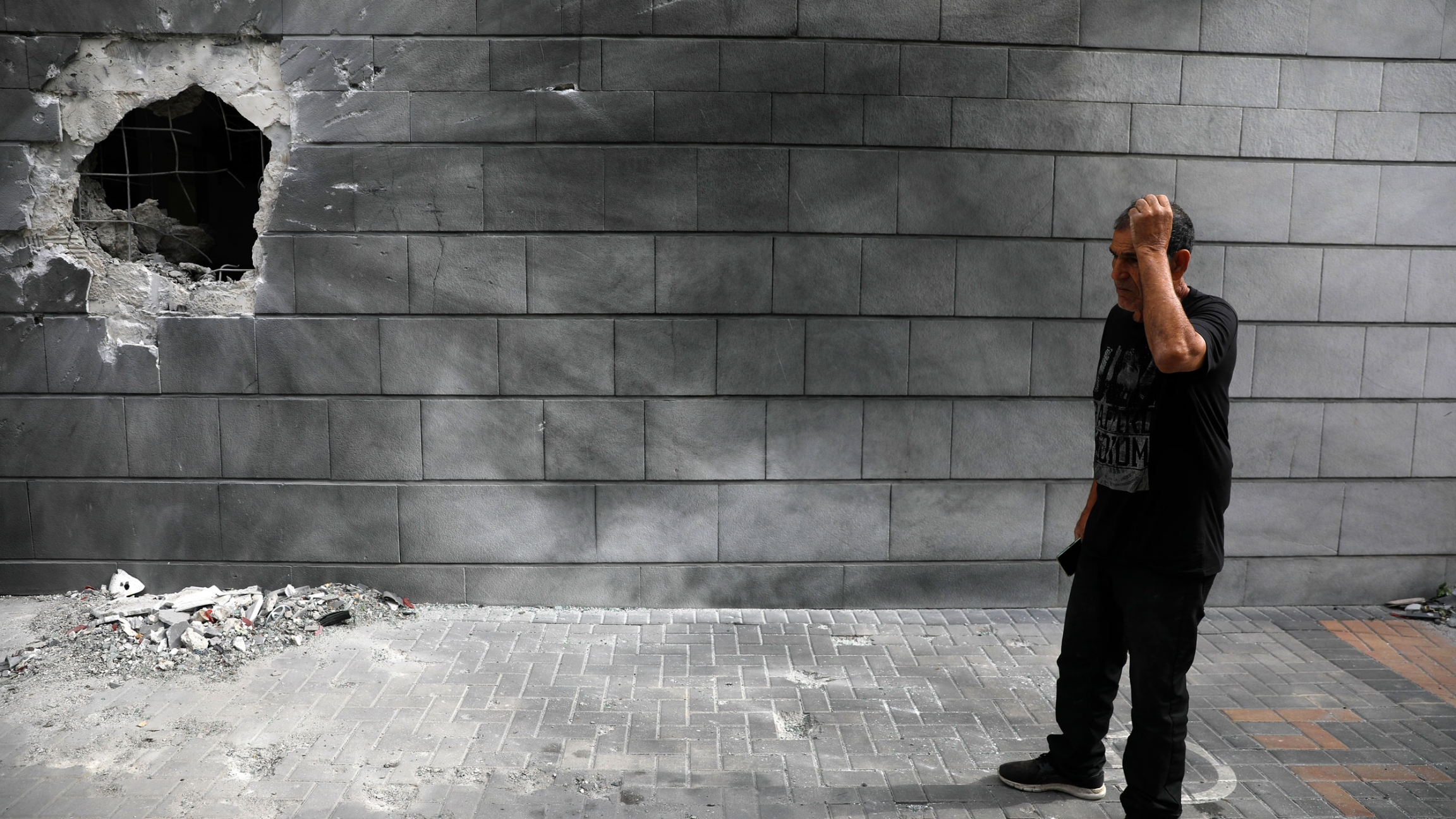 A man is show wearing a black t-shirt and pants while standing next to a cinder block wall with a large hole in it.