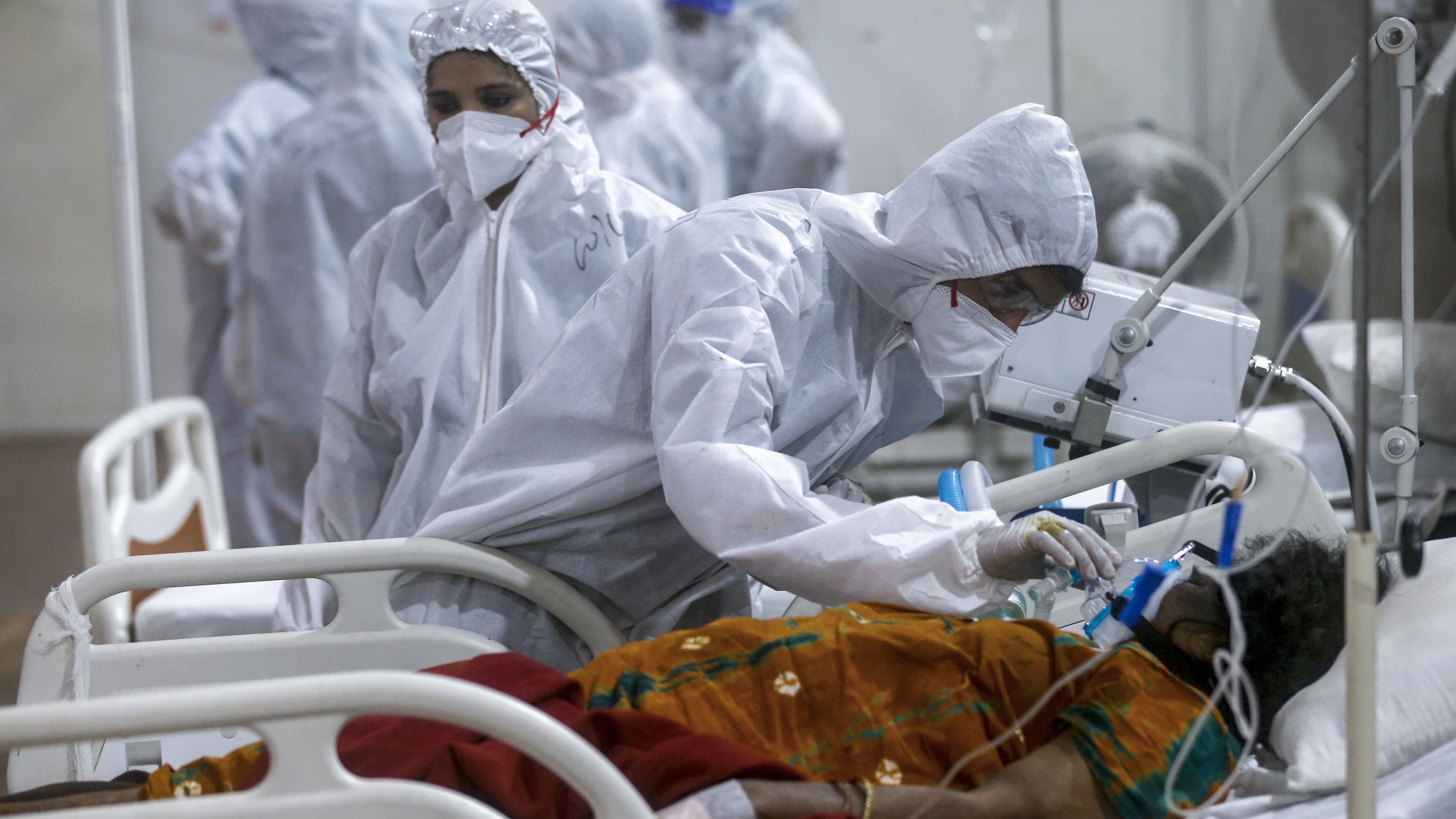 A health worker tries to adjust the oxygen mask of a patient at the BKC jumbo field hospital.