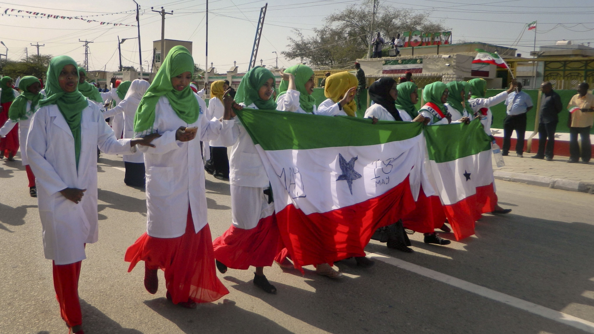 Women wear red, white, and green clothes and march in a parade celebrating independence.