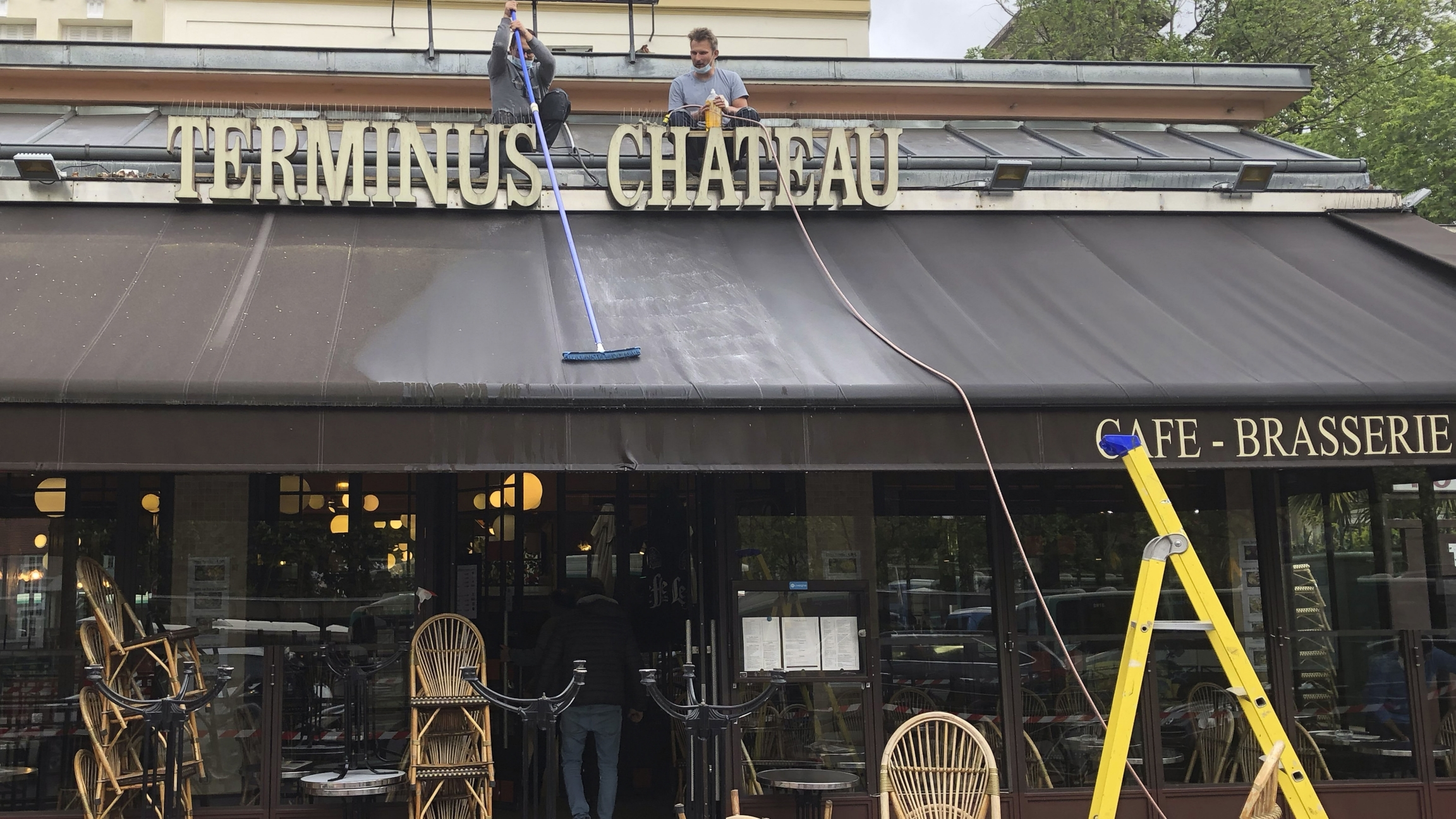 Restaurant workers clean the awning of a restaurant near Chateau de Vincennes.
