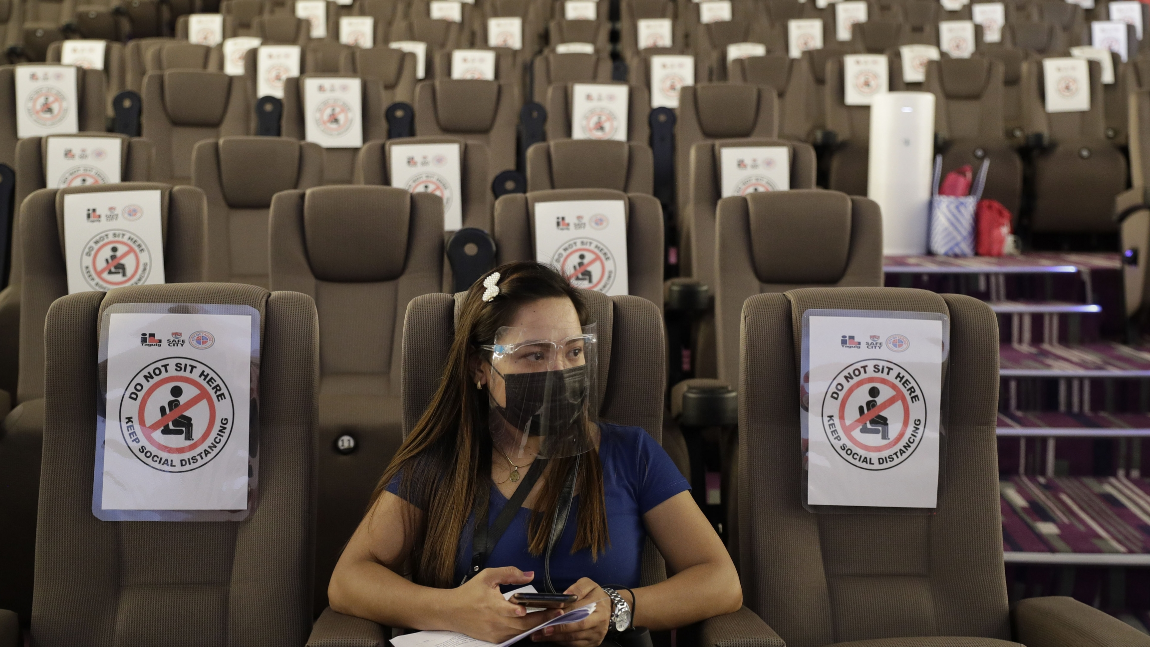 A sole woman waits in an empty movie theater-turned vaccination hub for her vaccine at a mall