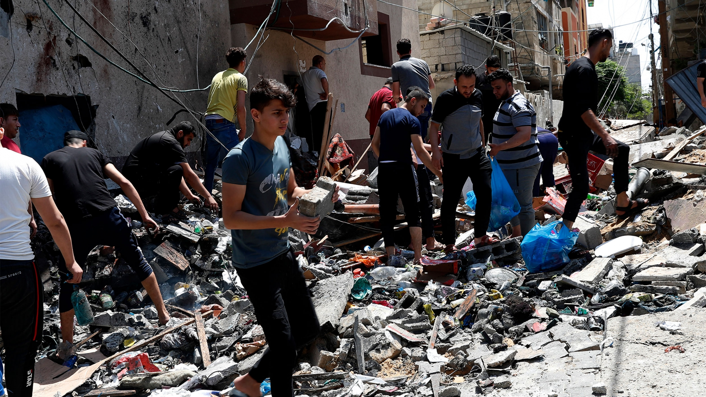 Young man in blue shirt lifts a piece of concrete as other men sift through rubble after an airstrike