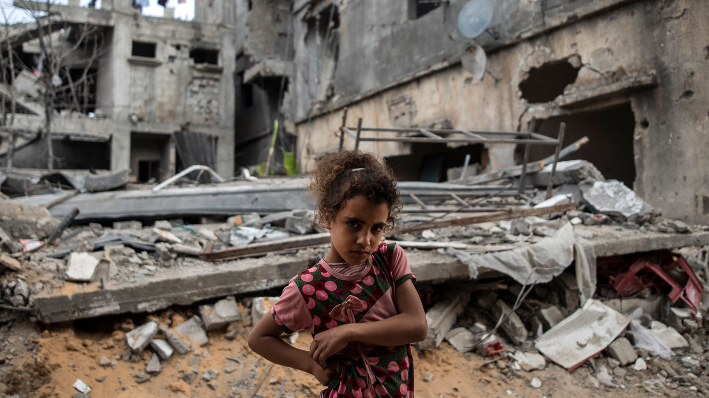 Girl stands in front of destroyed buildings