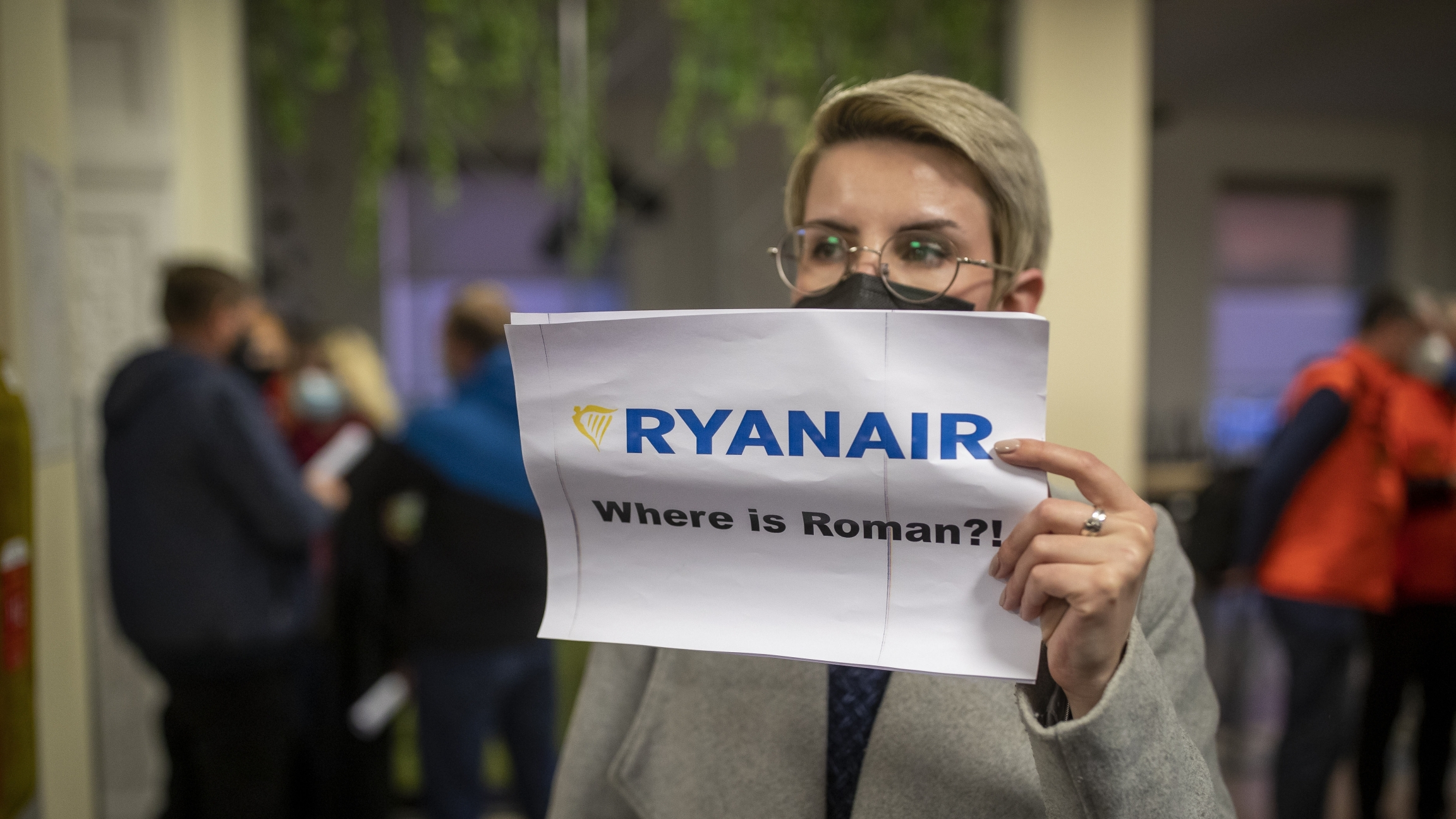 """A woman holds a poster reads, """"Where is Roman?""""as she waits to see passengers de-board Ryanair"""