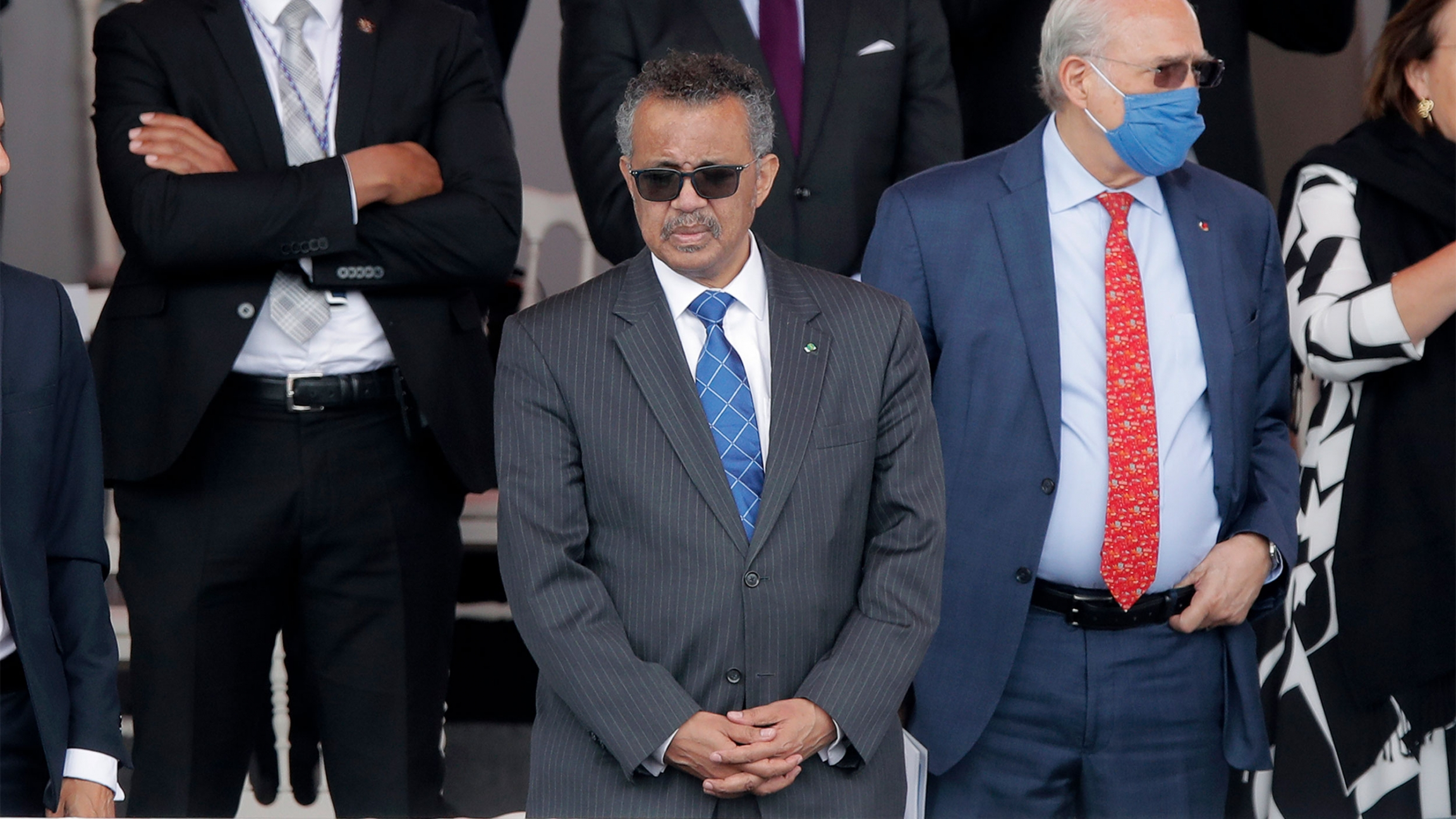 Men in suits, some wearing masks and sunglasses stand together