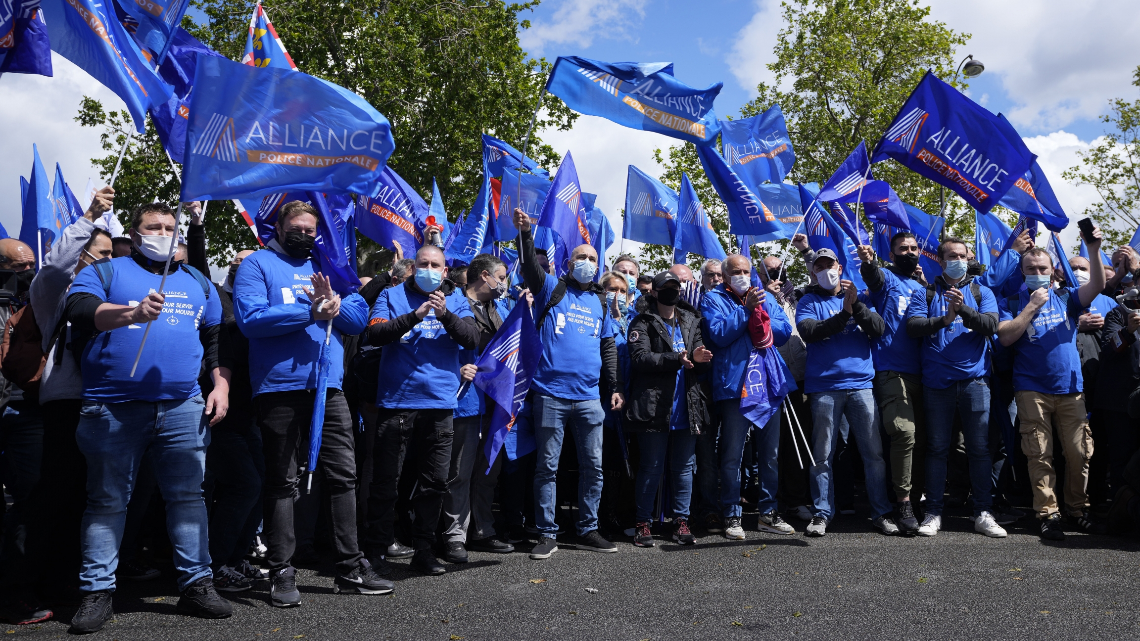French police officers wearing blue shirts and waving blue flags demonstrate Wednesday, May 19, 2021 in Paris. French police, feeling angry, vulnerable to attacks and useless