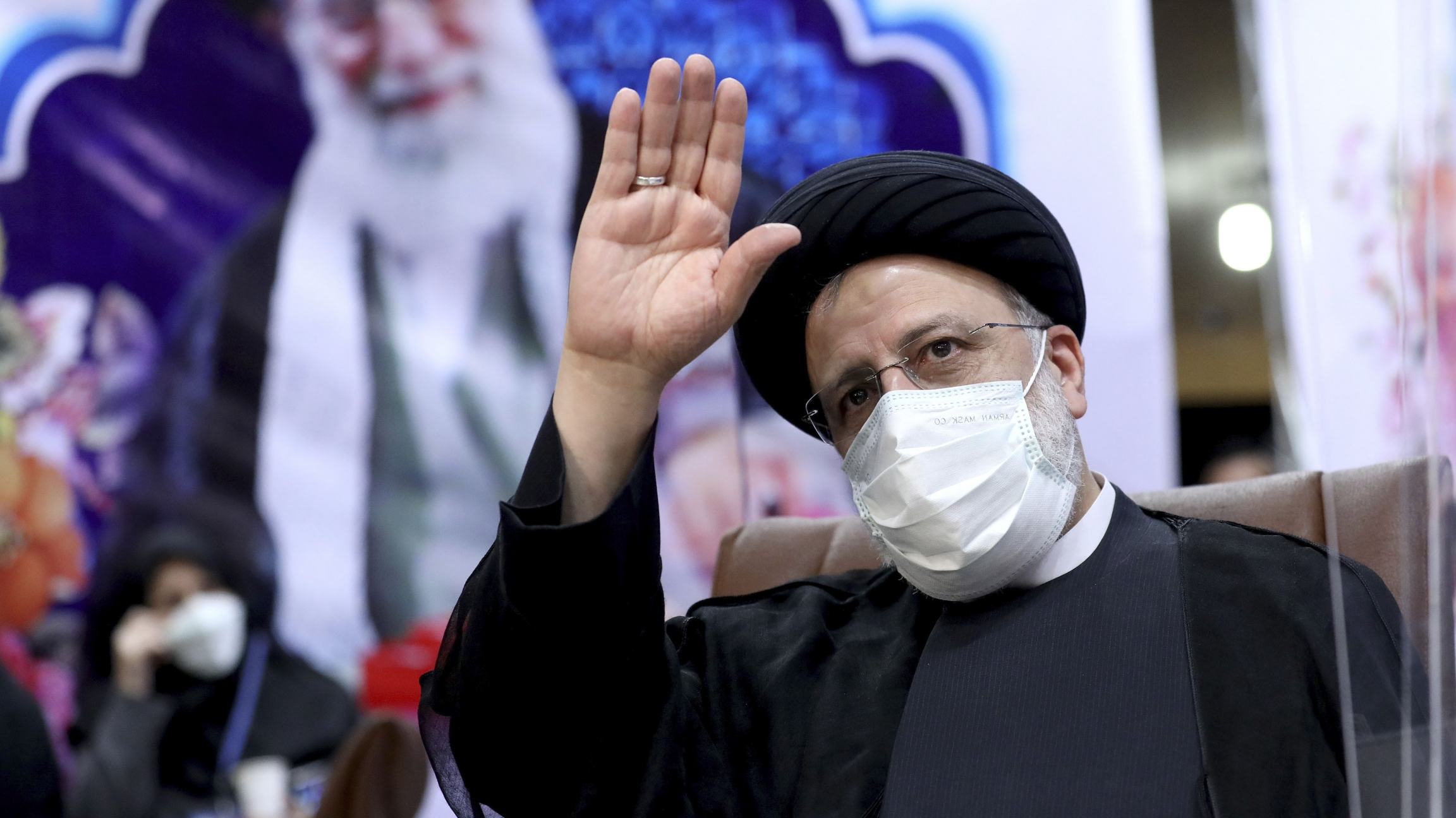 Iranian man in black robe and turban waves in front of a picture of Supreme Leader Ali Khamenei
