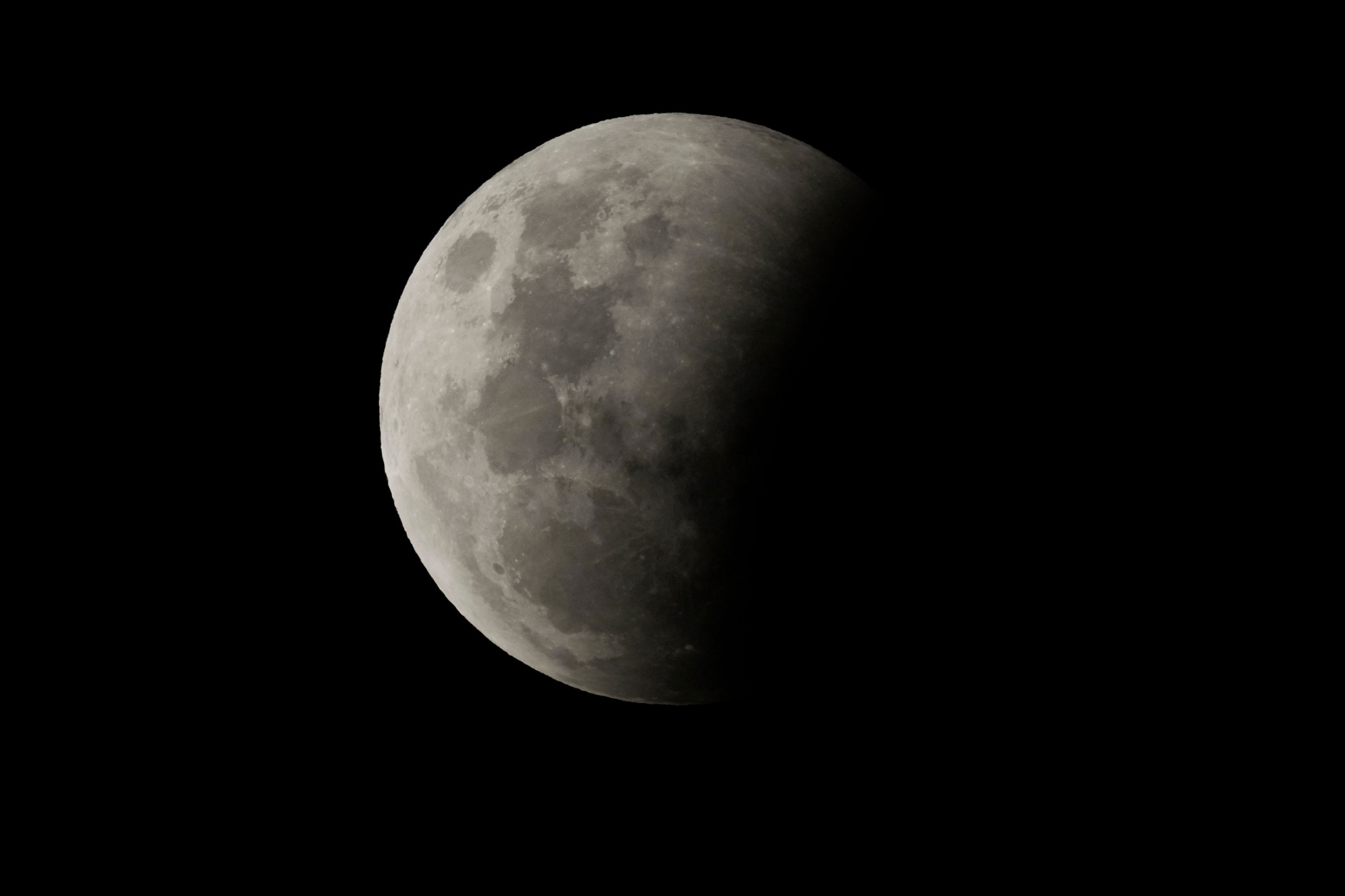 The beginning of a total lunar eclipse with a shadow on about 25% of the moon.